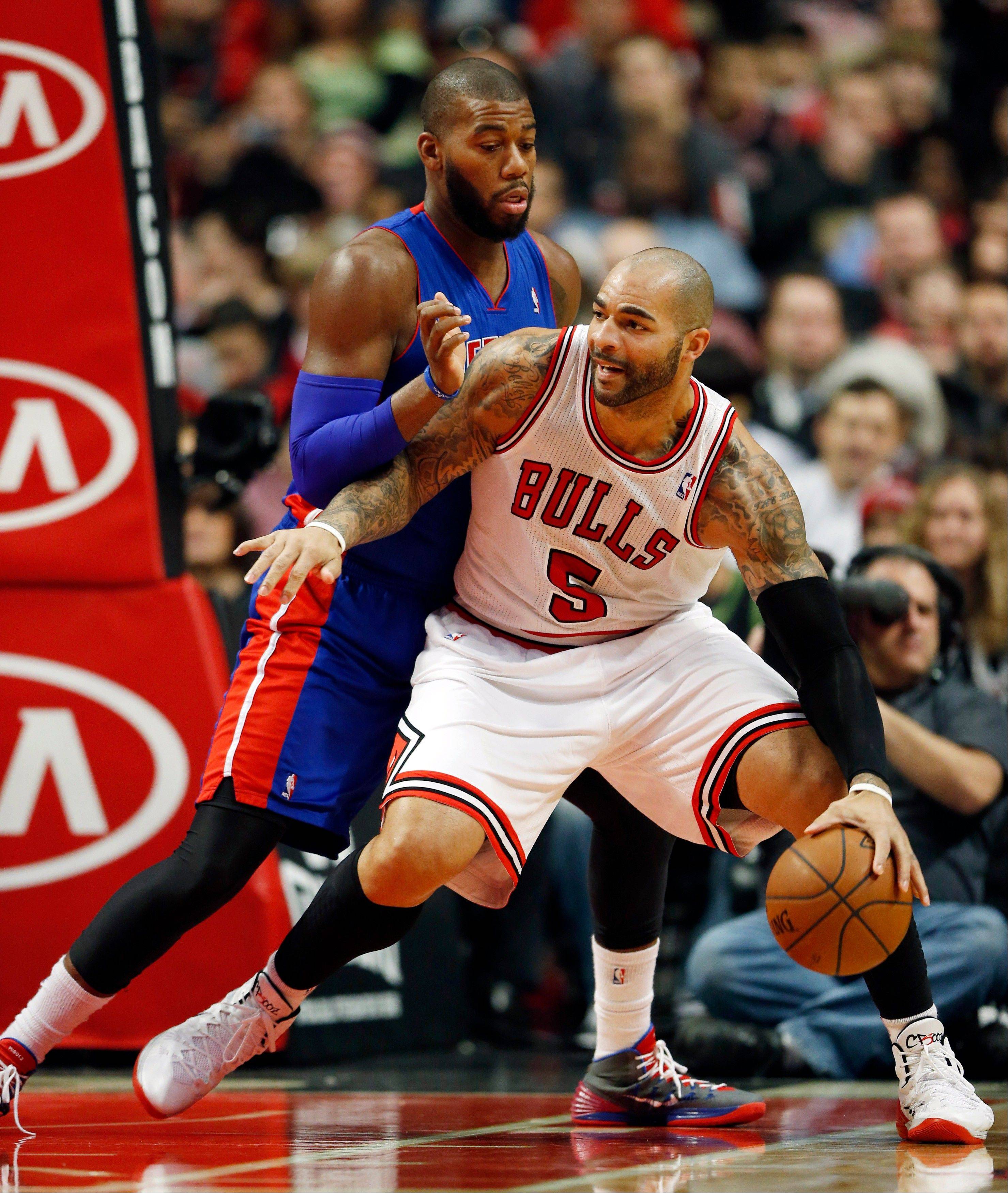 Bulls forward Carlos Boozer (5) looks for an opening against Detroit Pistons forward Greg Monroe during Saturday�s game. The Bulls lost to the Pistons, 92-75.
