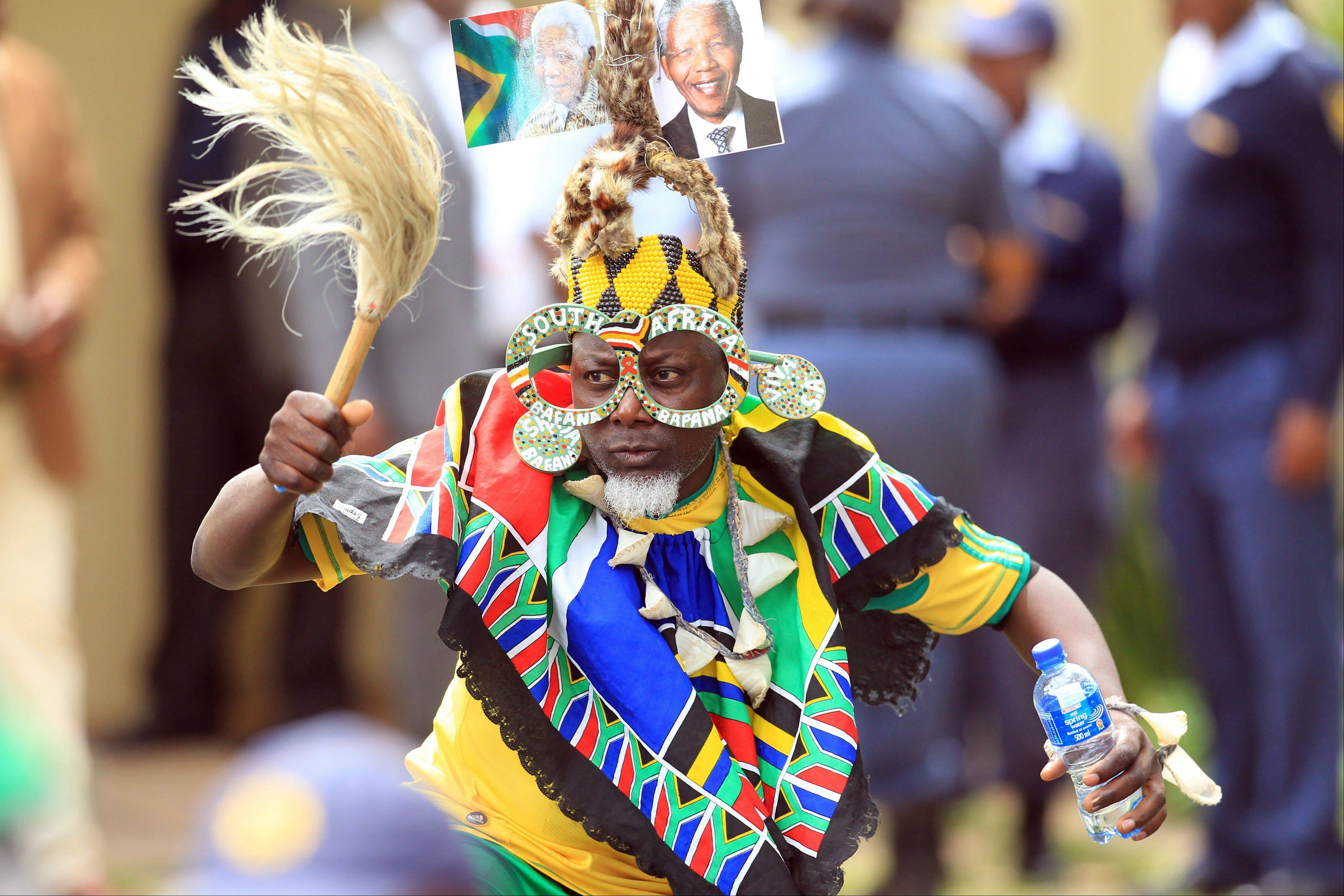 A soccer fan wearing a hat with portraits of former president Nelson Mandela, sings and dances Saturday in Johannesburg, South Africa.