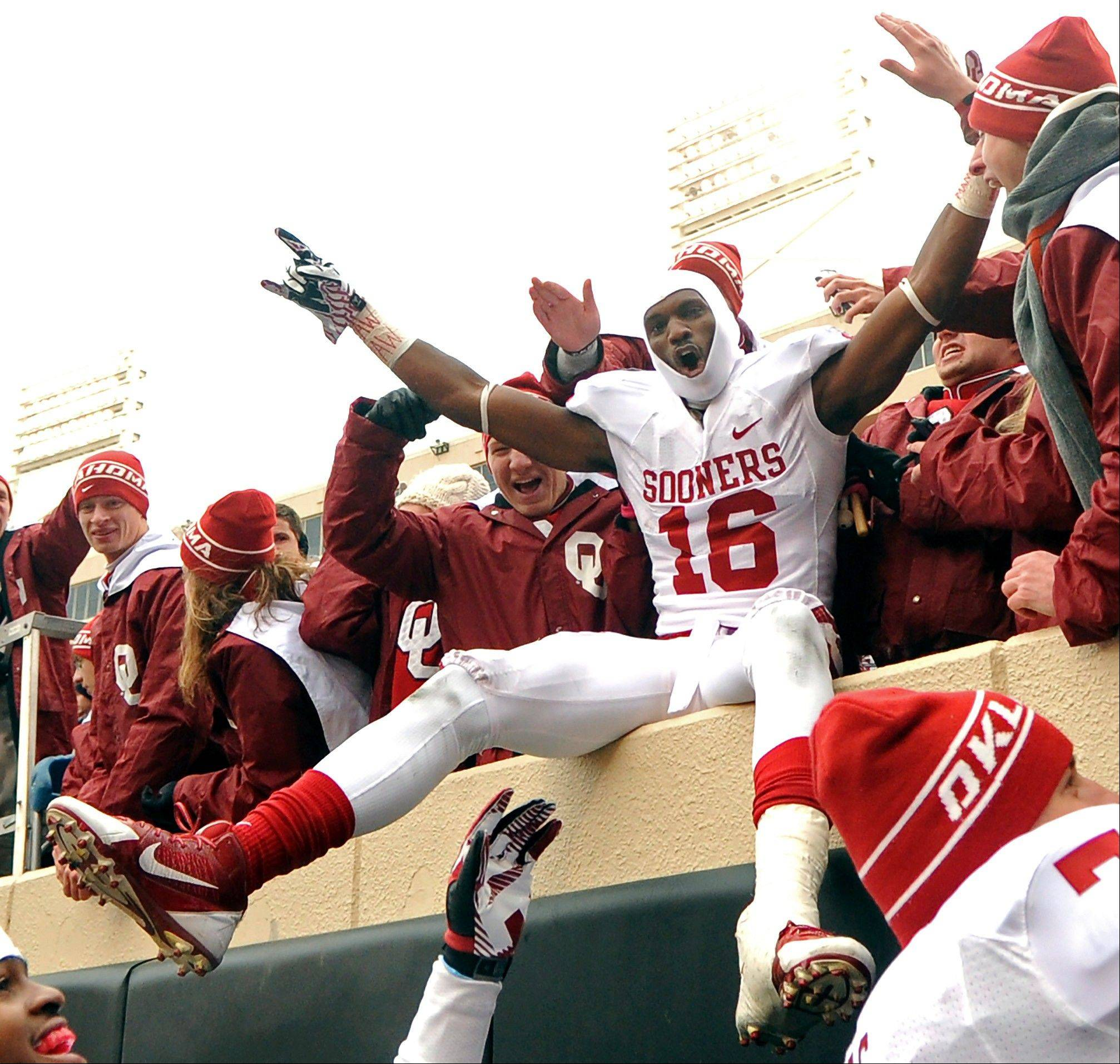 Oklahoma wide receiver Jaz Reynolds celebrates with fans after a 34-24 win over Oklahoma State on Saturday in Stillwater.