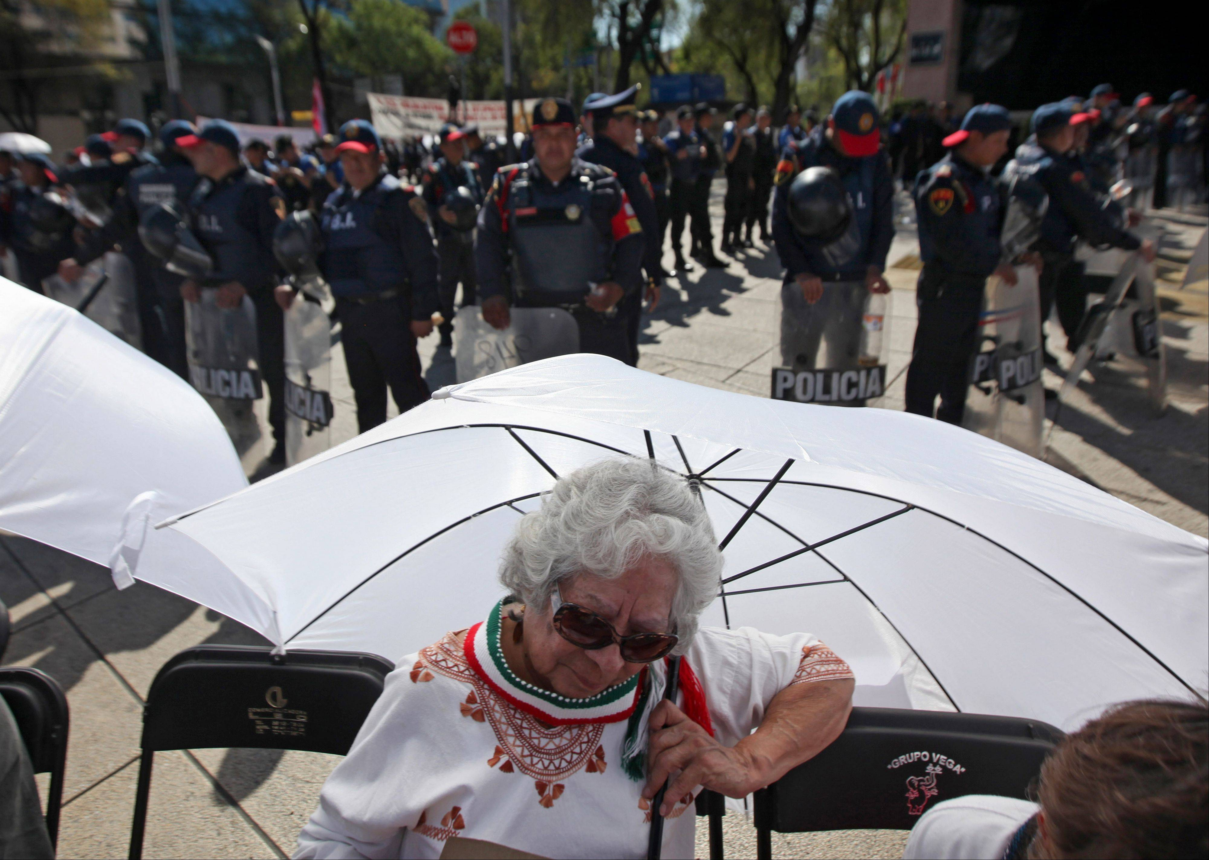 A protester sits under an umbrella Saturday in front of riot police outside the Mexican Senate building in Mexico City.