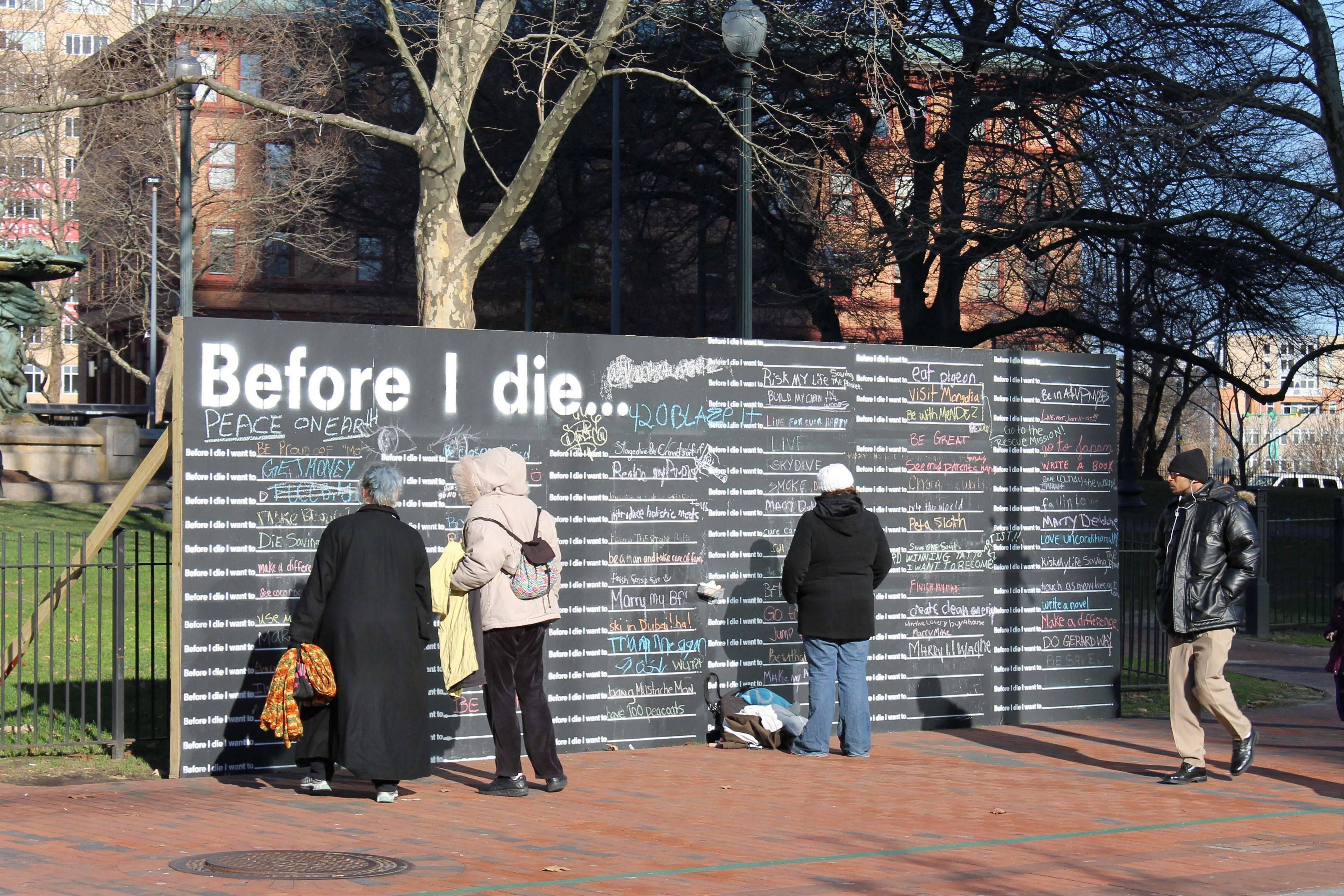 "People finish the sentence ""Before I die . . ."" on a large blackboard in Providence, R.I. Since 2011, 400 such walls have gone up in the United States as well as in 60 other countries. The global phenomenon has oversized blackboards, painted on buildings and freestanding displays that invite those passing by to complete the sentence."