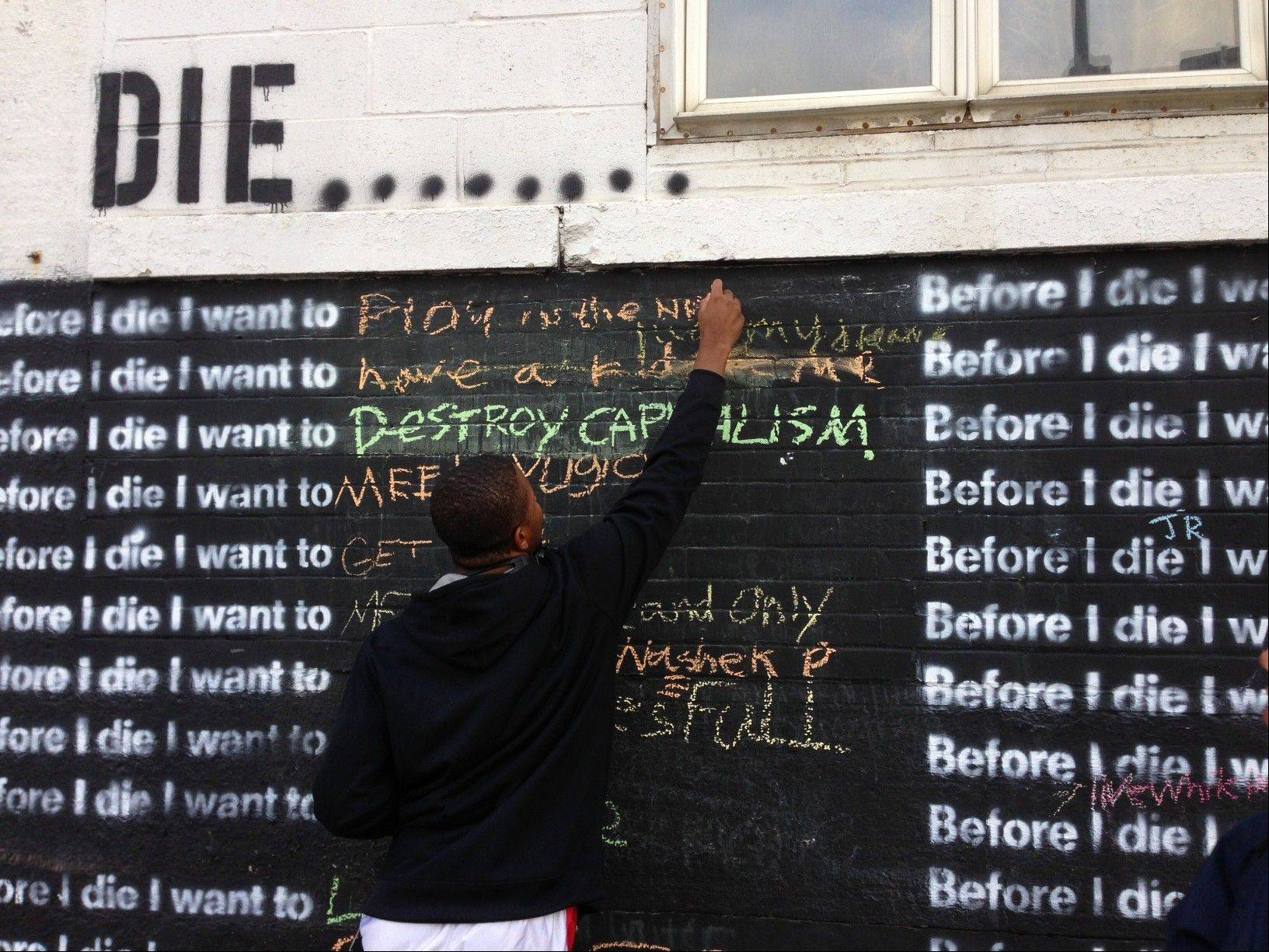 "Nyquis Turner, 16, writes ""Play in the NFL"" on a wall in Syracuse, N.Y., that invites passers-by to complete the sentence: ""Before I die, I want to..."" The global phenomenon started in 2011, when artist Candy Chang created the first wall on an abandoned house in her New Orleans neighborhood. More than 400 walls have gone up in the United States and more than 60 other countries."