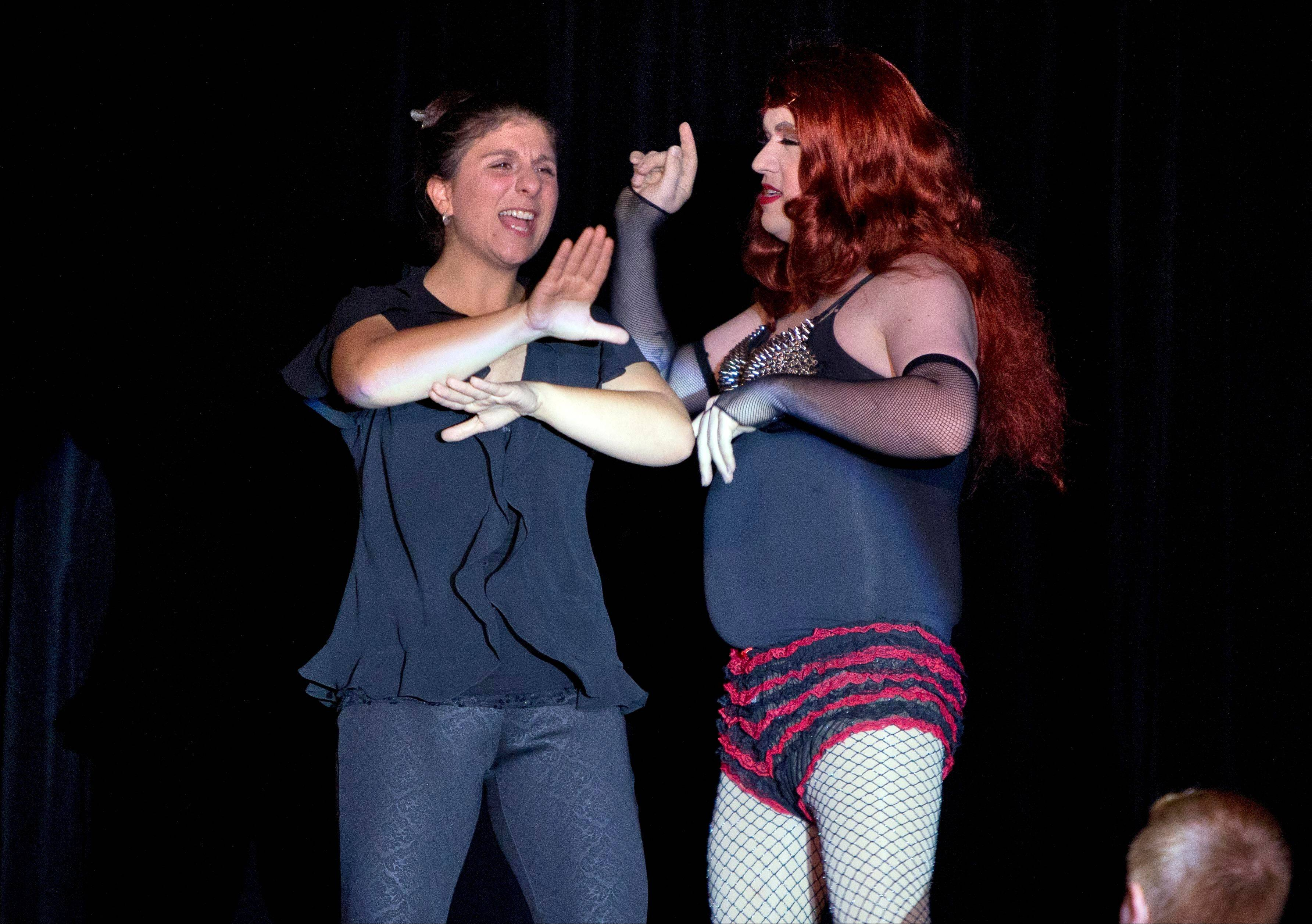 Holly Maniatty, left, an American Sign Language interpreter, signs during a performance by a contestant in the the Royal Majesty Drag Show and Competition in Portland, Maine. The 33-year-old has become an Internet sensation for the energetic way she uses dance moves, body language and American Sign Language to bring musical performances alive for those who can't hear.