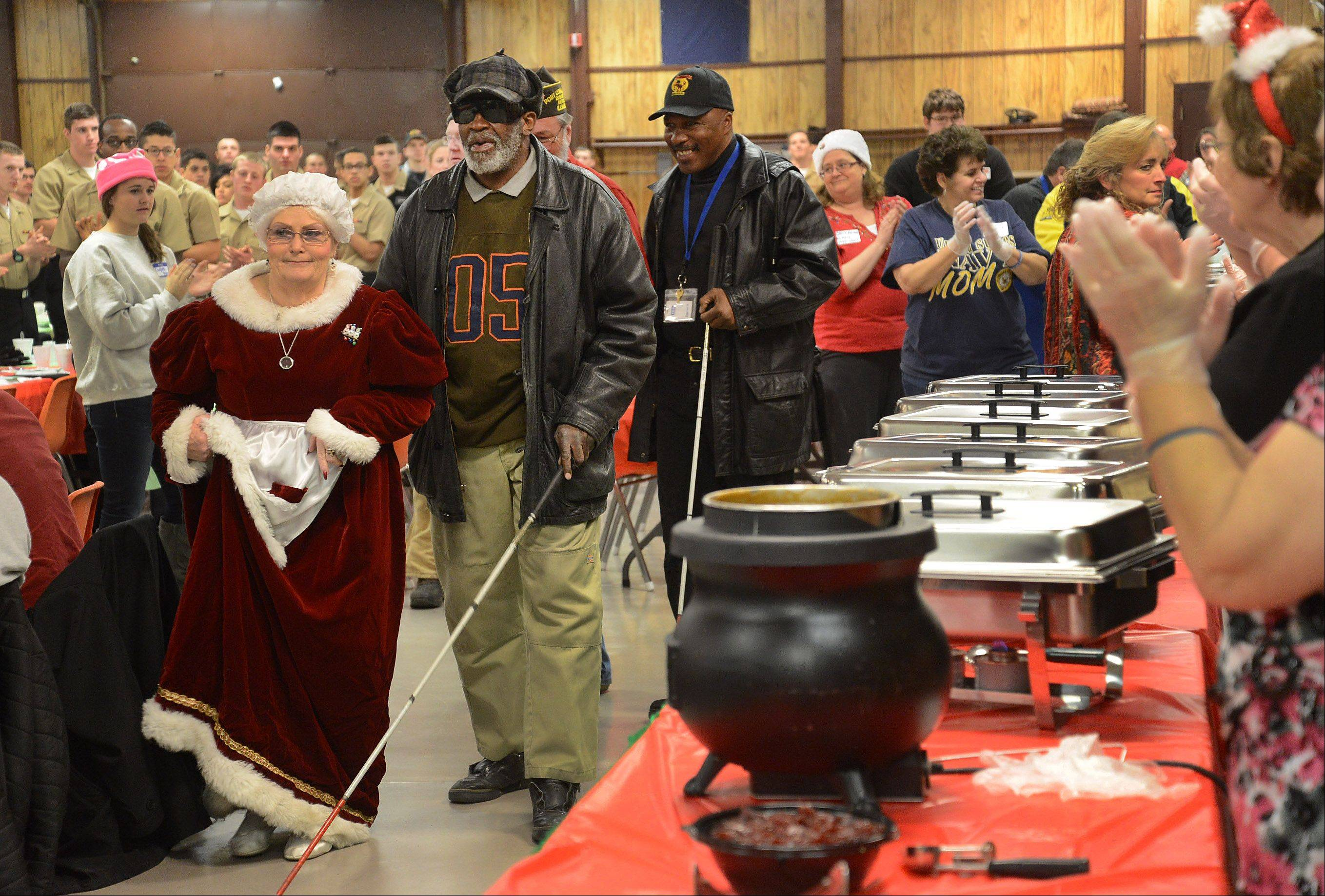 Mrs. Claus, aka Jan Oerly, helps to escort Rodney Williams of the blind unit from Hines VA Hospital to a table, as the VFW in Antioch hosted 350 sailors from Great Lakes and 50 veterans Saturday from Lovell and Hines hospitals for a full Christmas dinner.