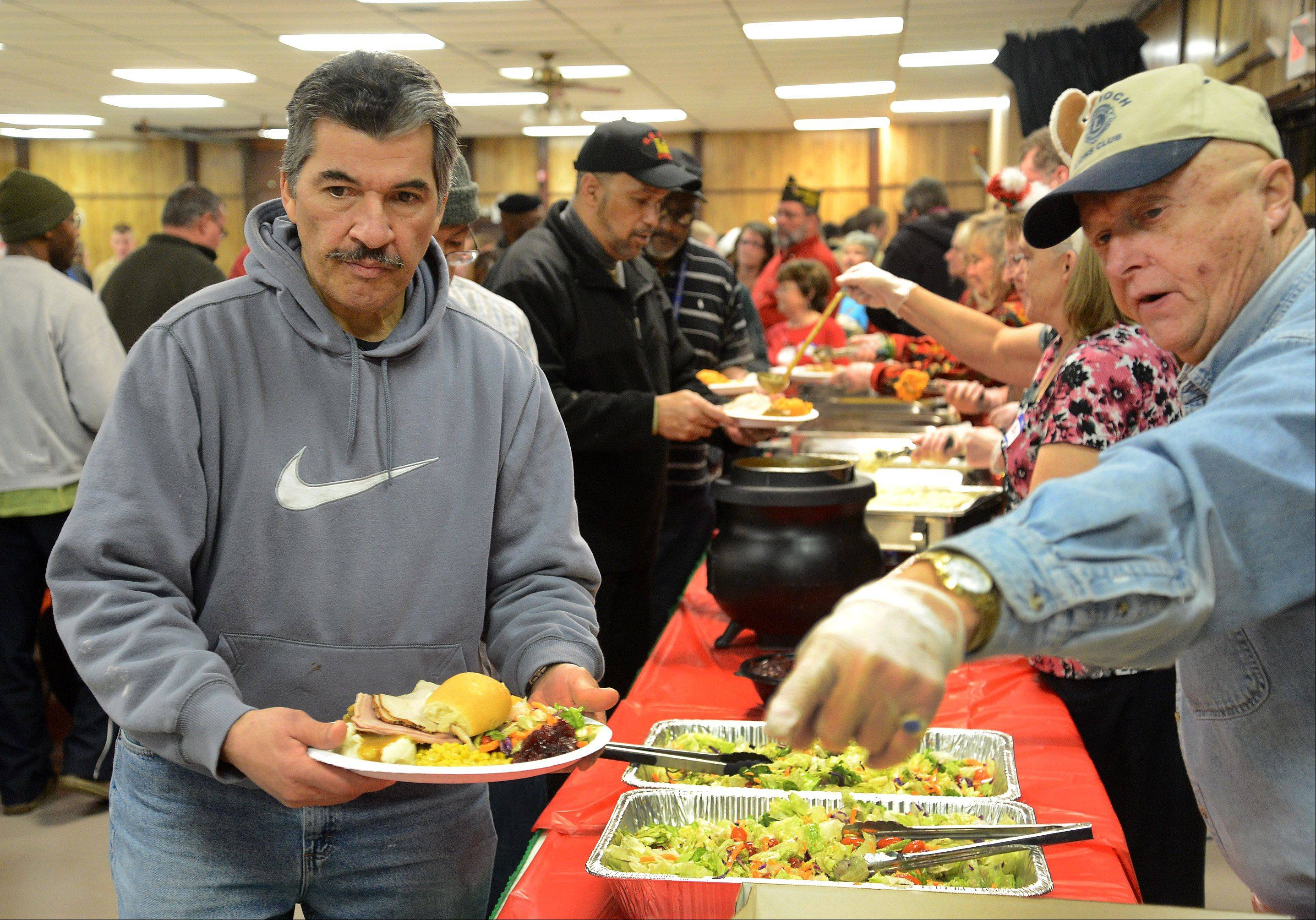 Volunteer Chuck Cermak of the Antioch Lions Club, right, serves up a roll for Howard Gibson of the Capt. James Lovell Federal Health Care Hospital in North Chicago, as the VFW in Antioch hosted 350 sailors from Great Lakes and 50 veterans from Lovell and Hines hospitals Saturday for a full Christmas dinner.