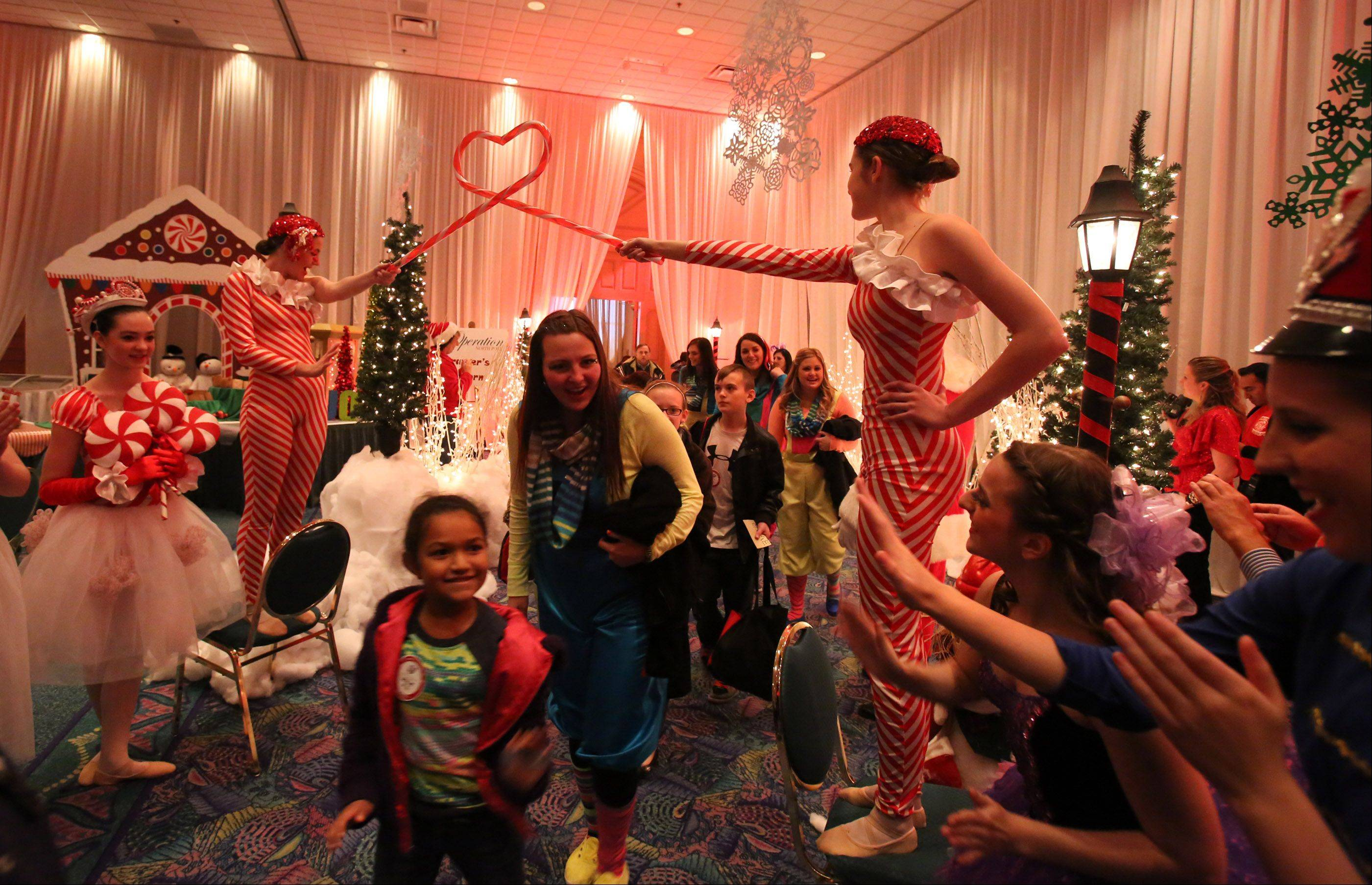 Families are led into Santa's Winter Wonderland during Operation North Pole Saturday at the Donald E. Stephens Convention Center in Rosemont.