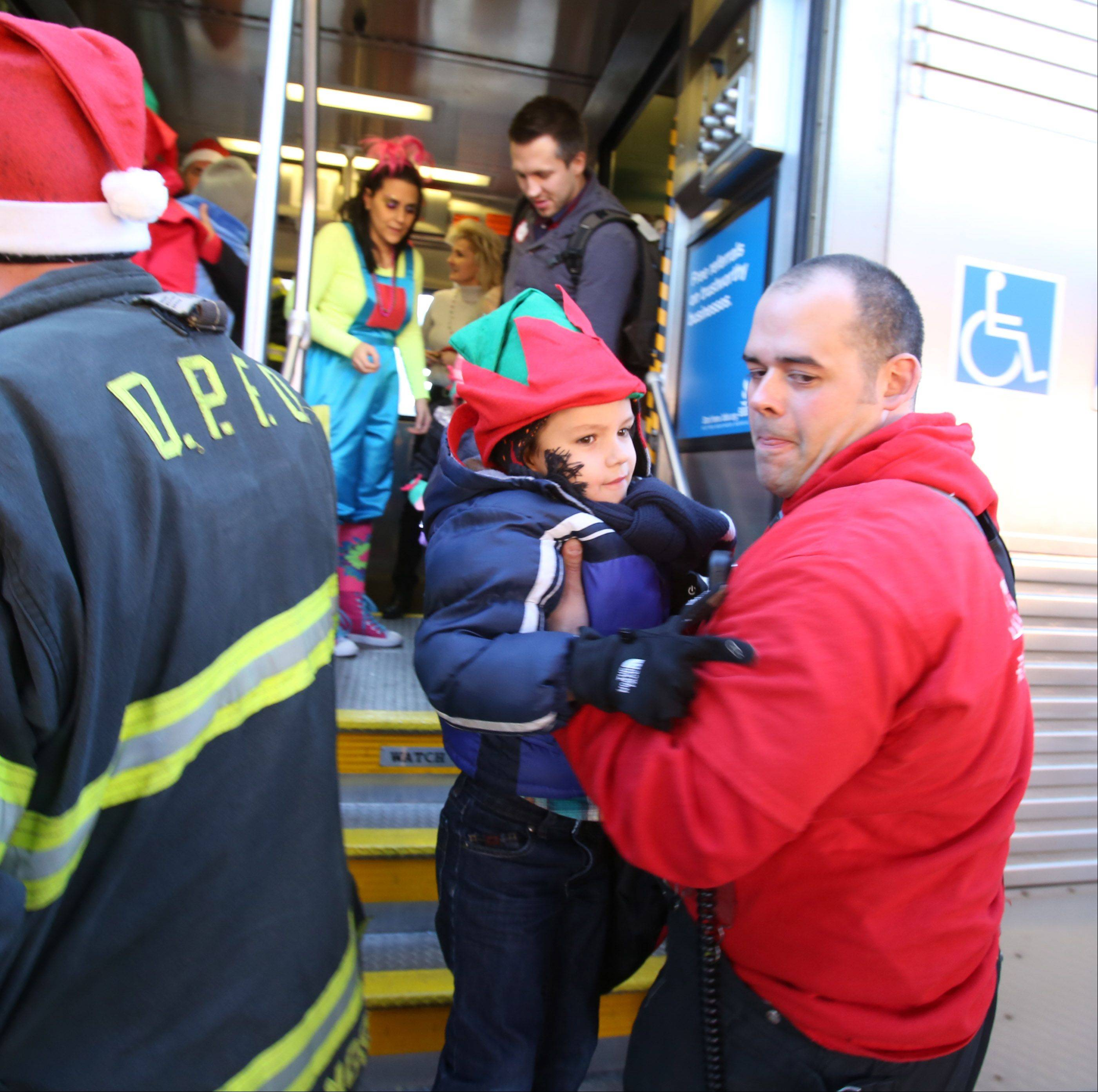 Ed Rodgers, firefighter with Des Plaines Fire Department, lifts Marek Szklane, 5, of Lombard off the train Saturday during Operation North Pole in Des Plaines.