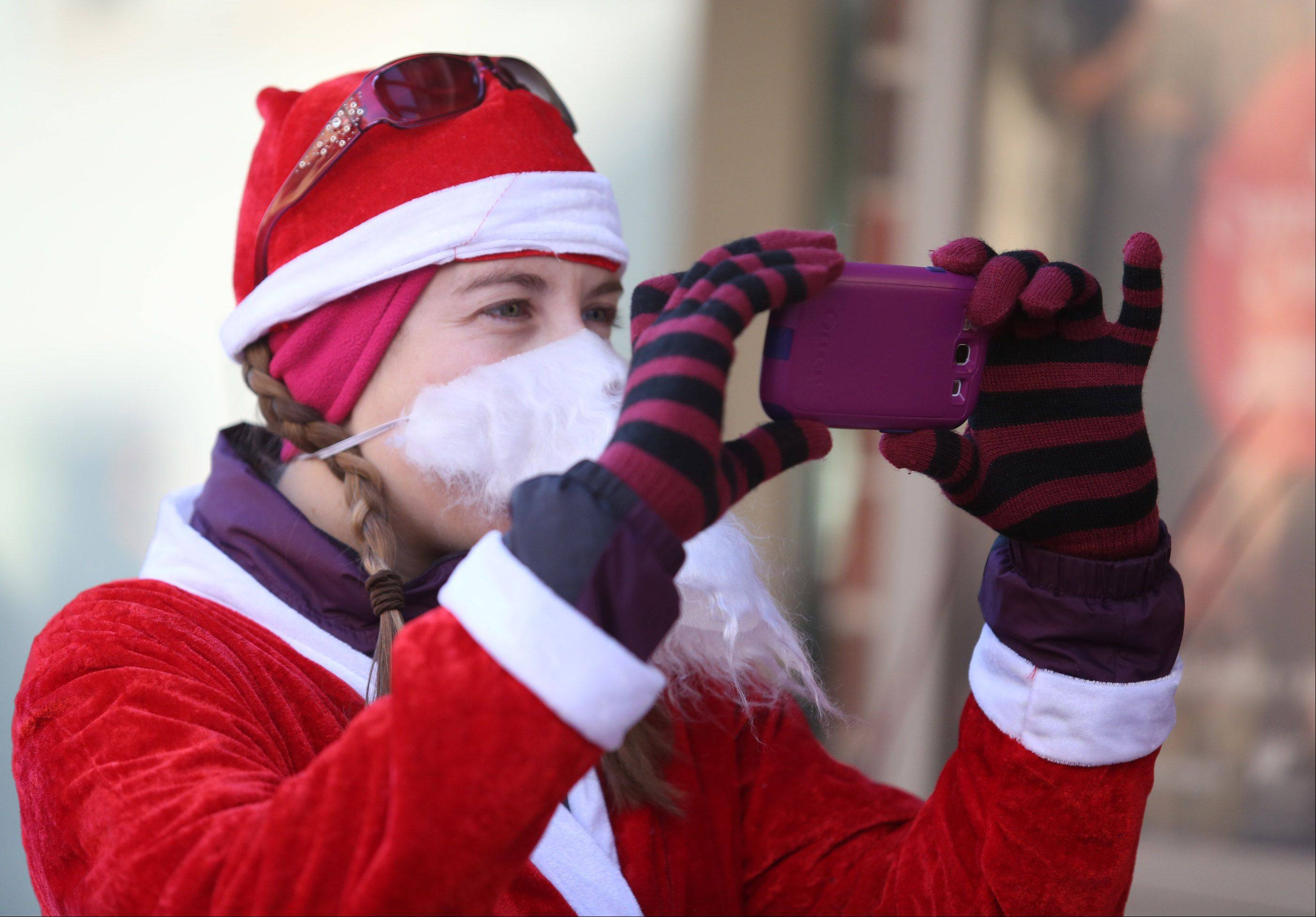 Katie Deswardt of Lake Zurich uses her costume beard to keep warm while taking photos Saturday at the Rotary Santa Run in Arlington Heights.