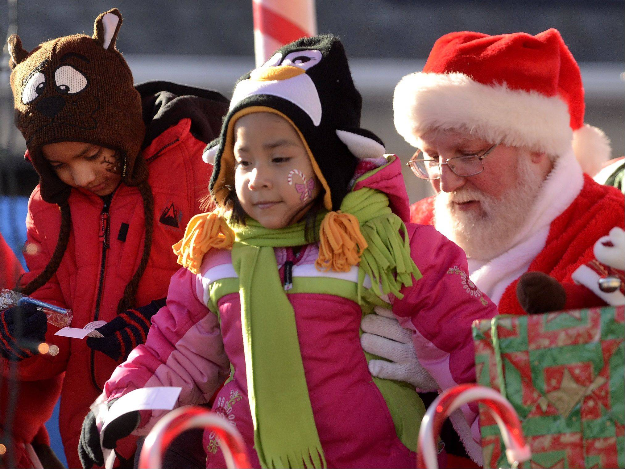 Aaron, left, and Nora Basilio of Wauconda visit with Santa on Saturday at Wauconda's Holiday Walk on Main Street.