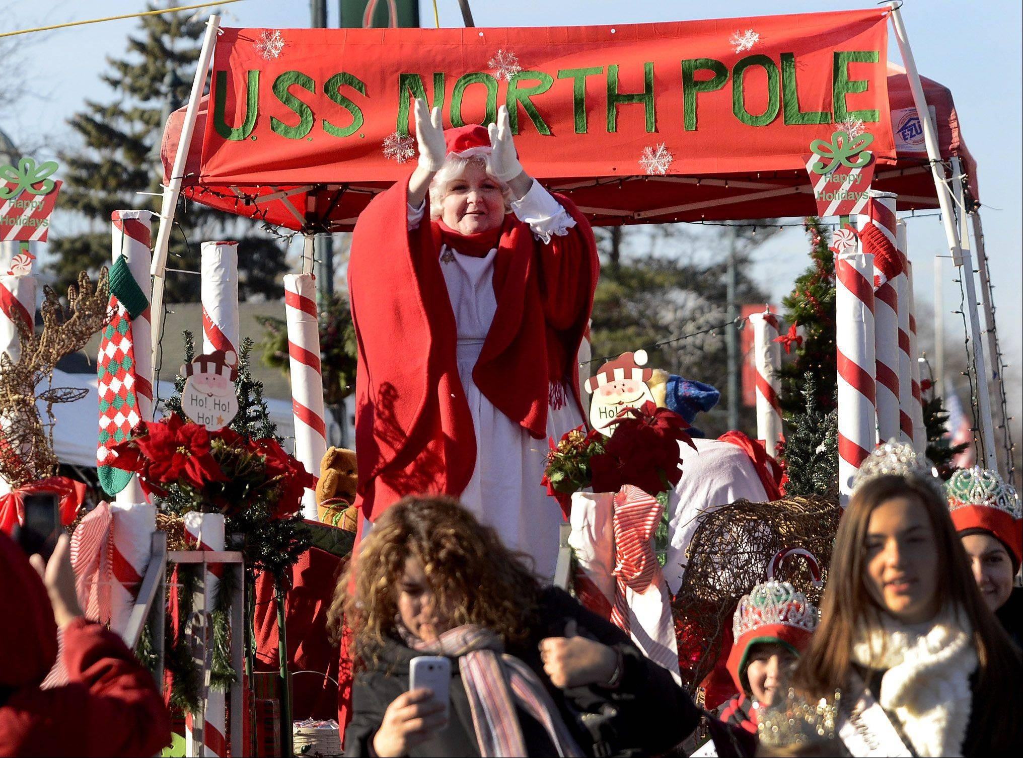 Mrs. Claus applauds the arrival of Santa on Saturday at Wauconda's Holiday Walk on Main Street.