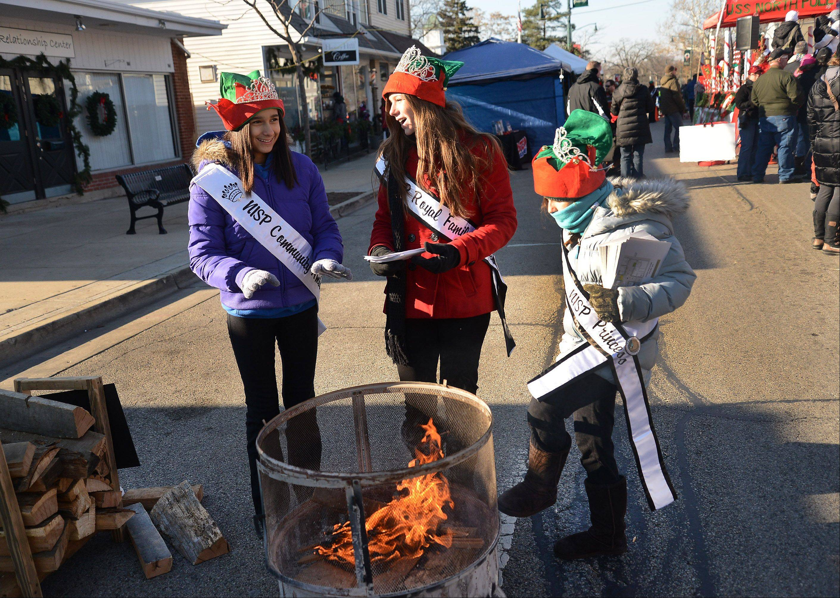 From left, Serenity Perez, Kara Pohlman and Abby Hammer try to keep warm Saturday during Wauconda's Holiday Walk on Main Street. All three belong to the Northern Illinois Scholarship Program, which embraces community service and helping others.