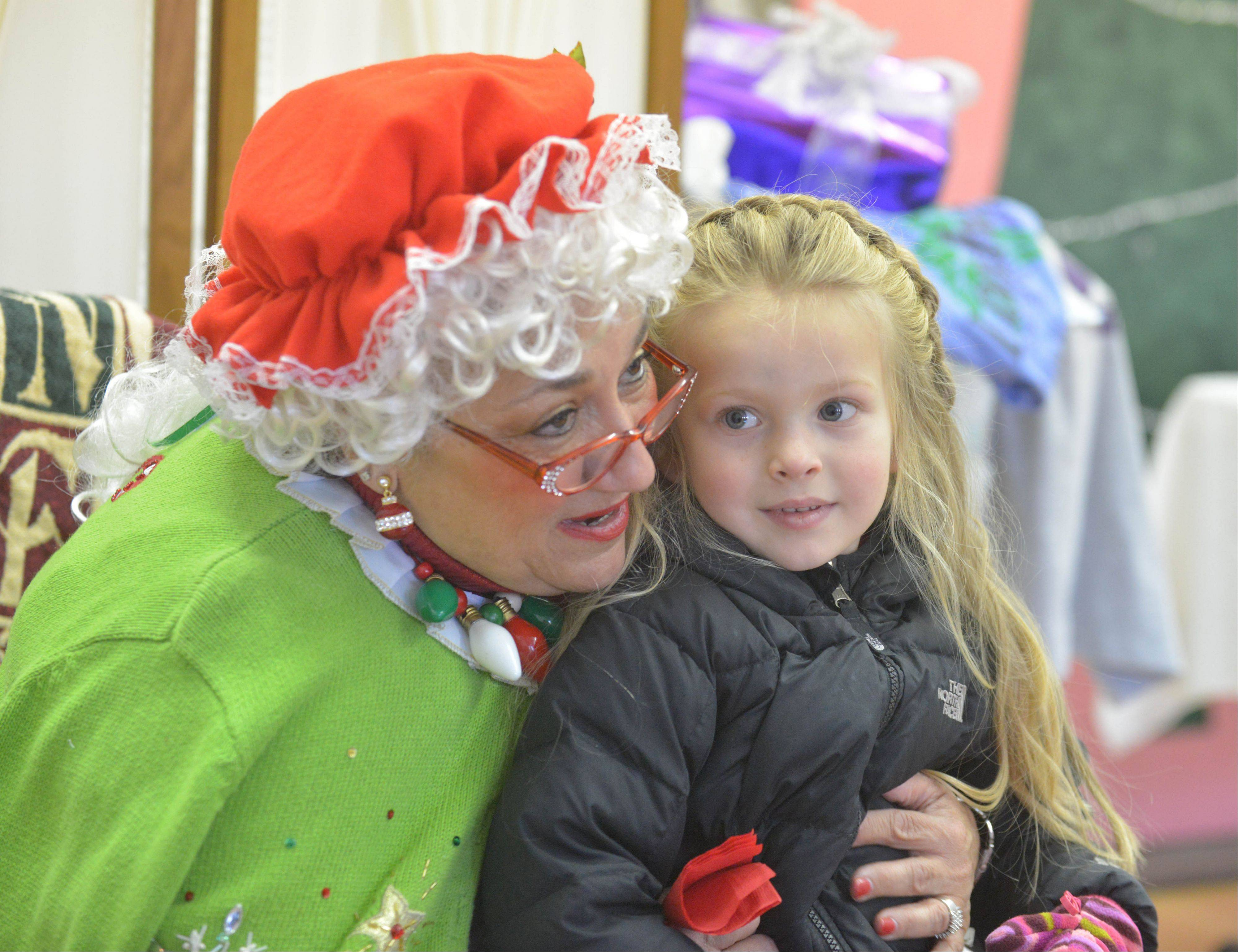 Mrs. Claus chats with Mira Snyder, 4, of Lombard during Lombard's Jinglebell Jubilee on Saturday