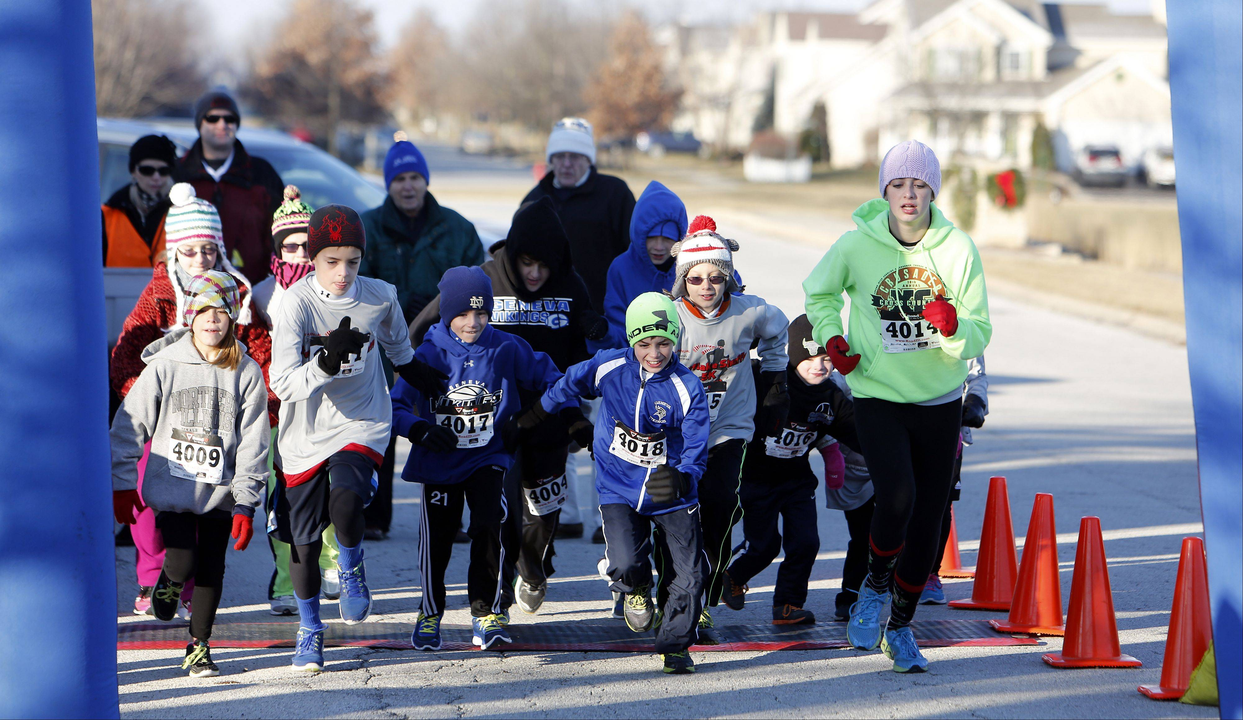 Kids take off at the start of the one-mile fun run during the TriCity Family Services' fifth annual Snowflake Shuffle Saturday in Geneva.