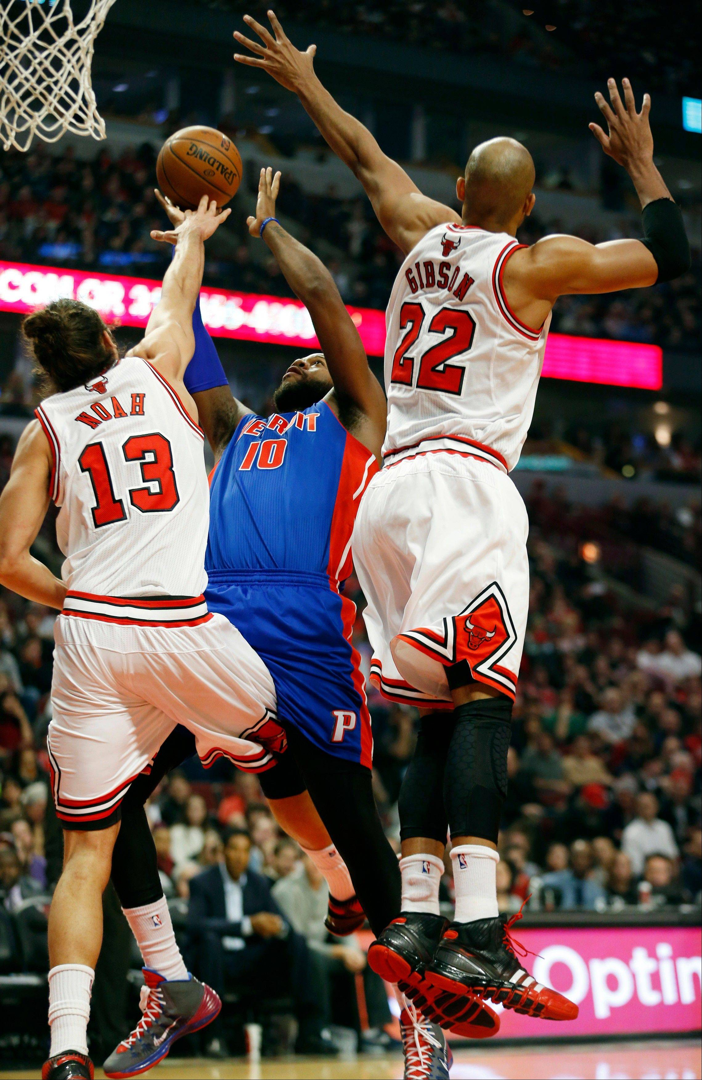 The Pistons' Greg Monroe drives to the basket against the Bulls' Joakim Noah and Taj Gibson on Saturday at the United Center.