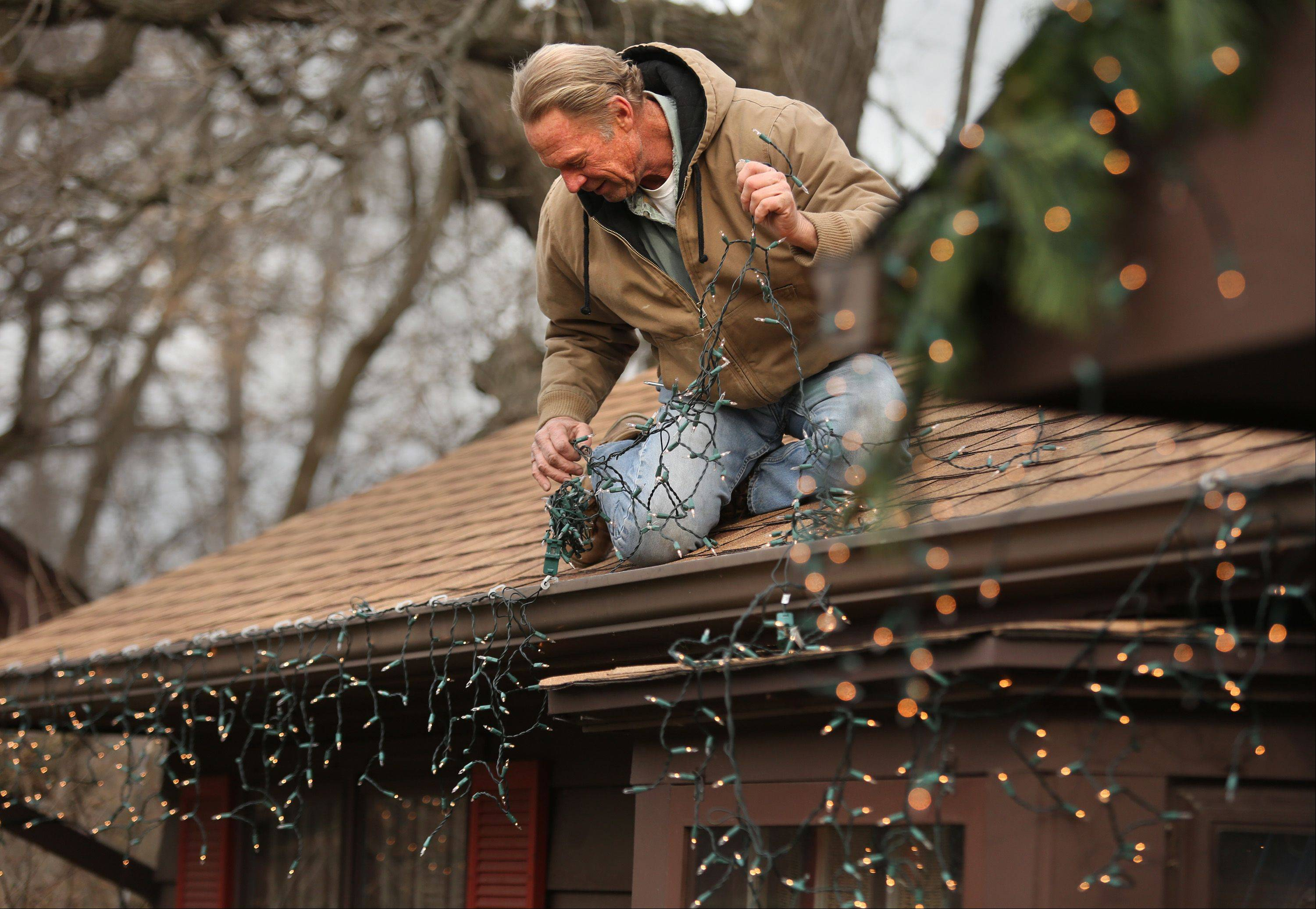 Steve Patzer, of St. Charles, decorates his house with Christmas lights Monday. His three daughters are coming home for the holiday, along with some spouses and even three grandchildren. He says he began decorating the house to surprise the girls when they would come home from college, and he�s been keeping the tradition going every year since.