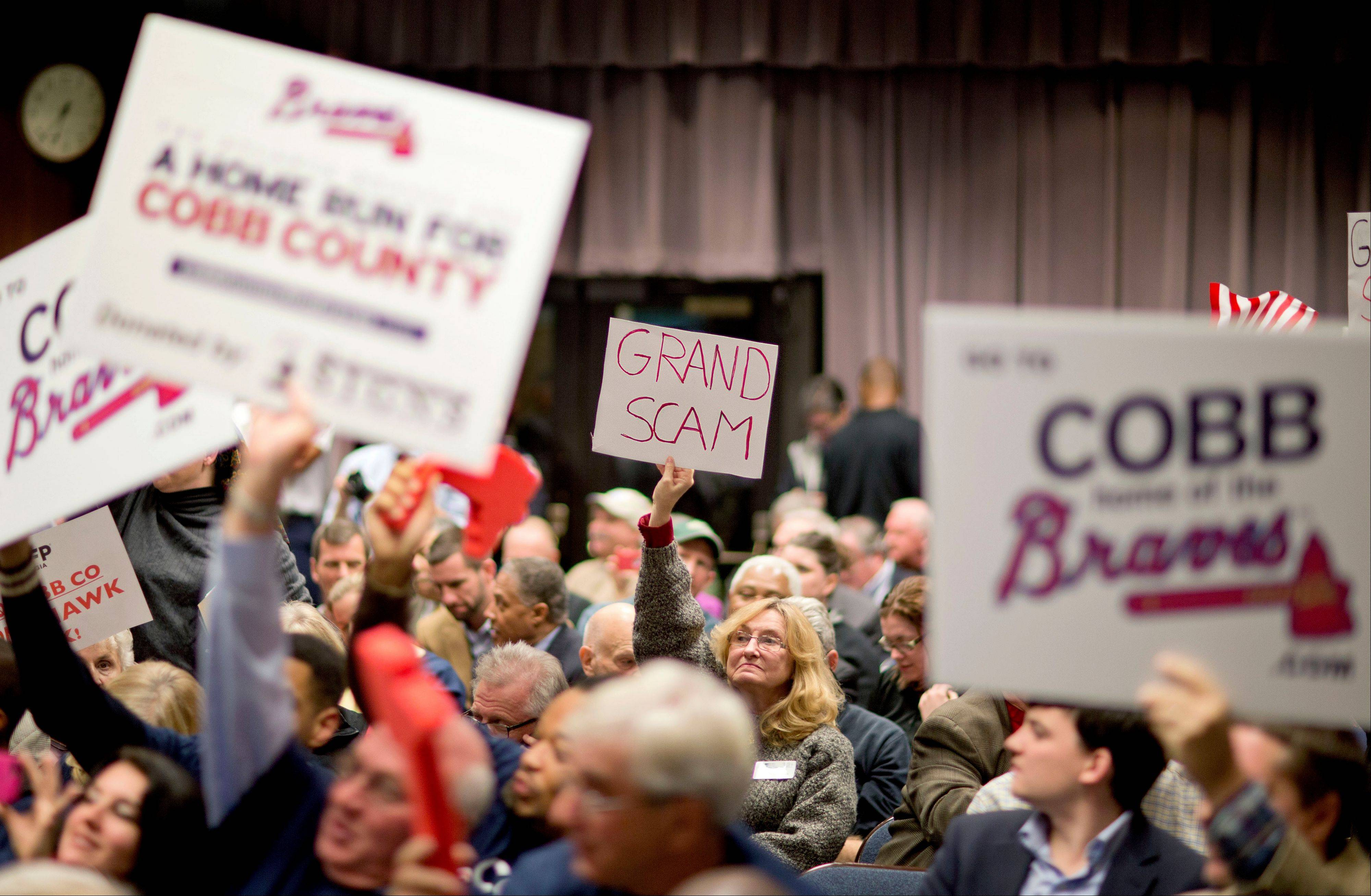 Proponents and opponents of a plan for the Atlanta Braves to build a new baseball stadium in Cobb County hold up their respective signs before the start of a Cobb County commission hearing on the subject, in Marietta, Ga., Nov. 26.