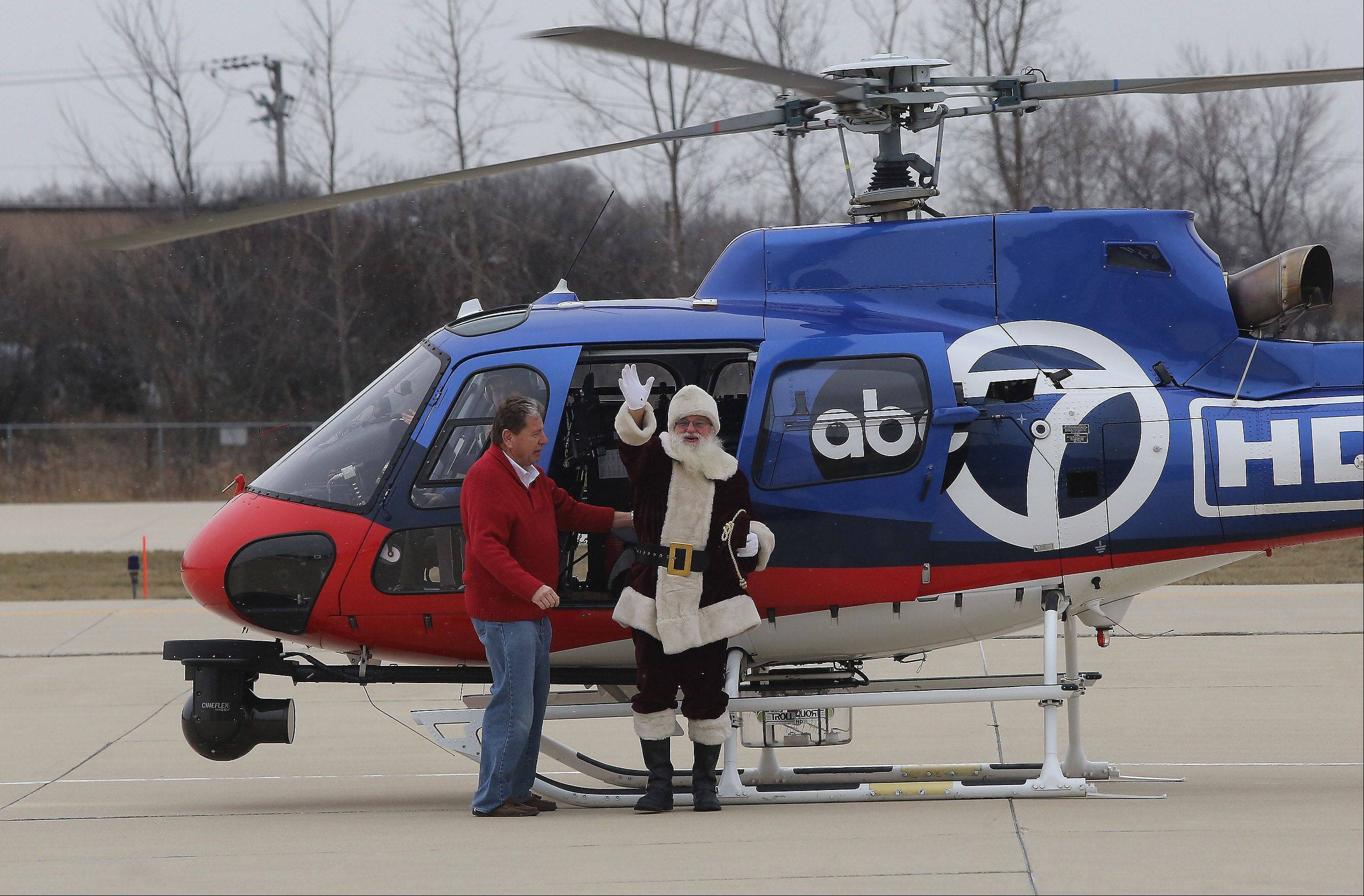 Northwest Flyers President J.P. Skip Barchfeld helps Santa get out of a helicopter Sunday as he arrives for Santa�s Flight to Schaumburg at the Schaumburg Regional Airport. The holiday event, sponsored by the Schaumburg Park District and The Northwest Flyers, drew about 300 to the airport for a visit with Santa, along with games and crafts.