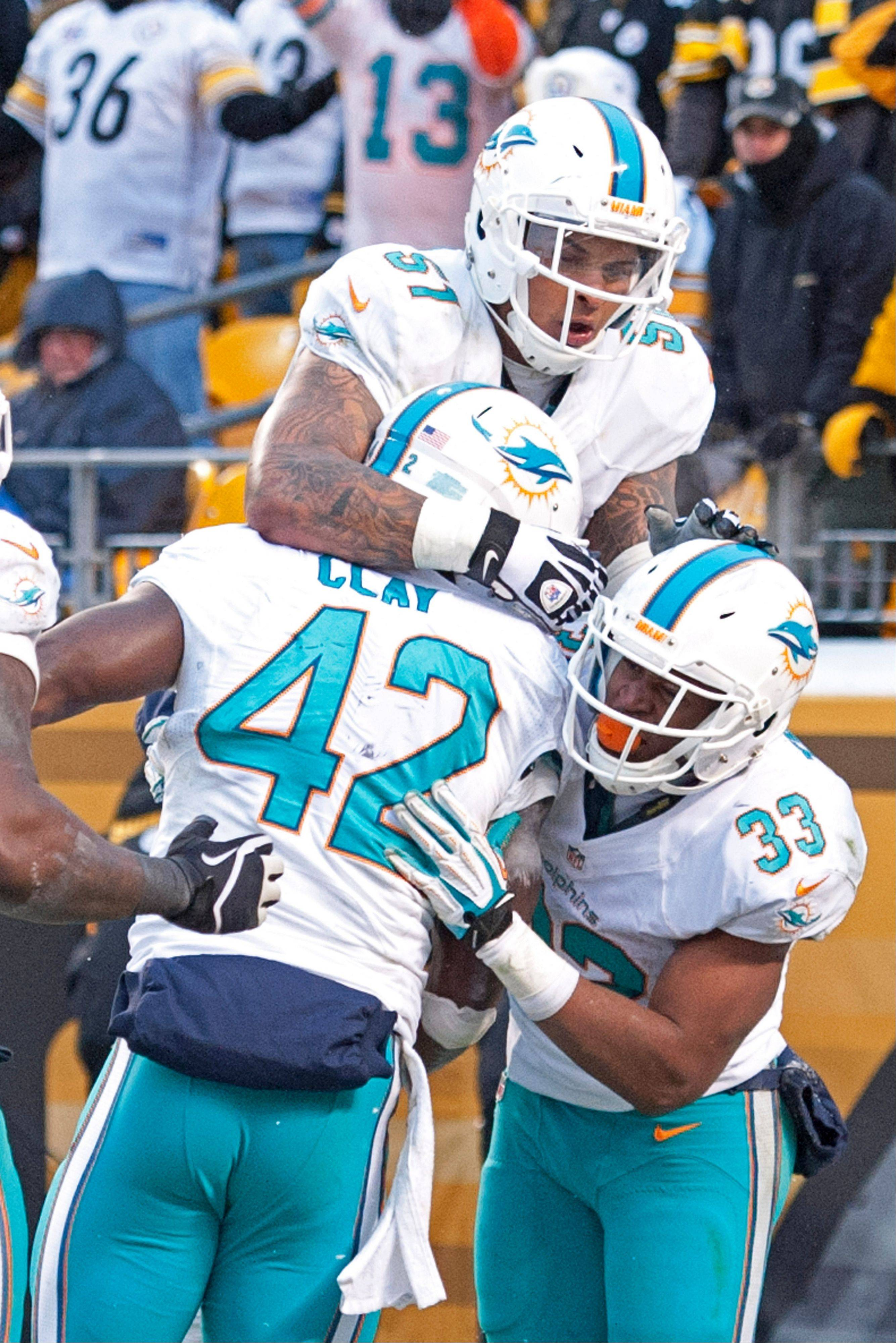 Miami Dolphins tight end Charles Clay (42) celebrates with Mike Pouncey (51) and Daniel Thomas (33) after scoring a touchdown during the second half of an NFL football game against the Pittsburgh Steelers in Pittsburgh, Sunday, Dec. 8, 2013.