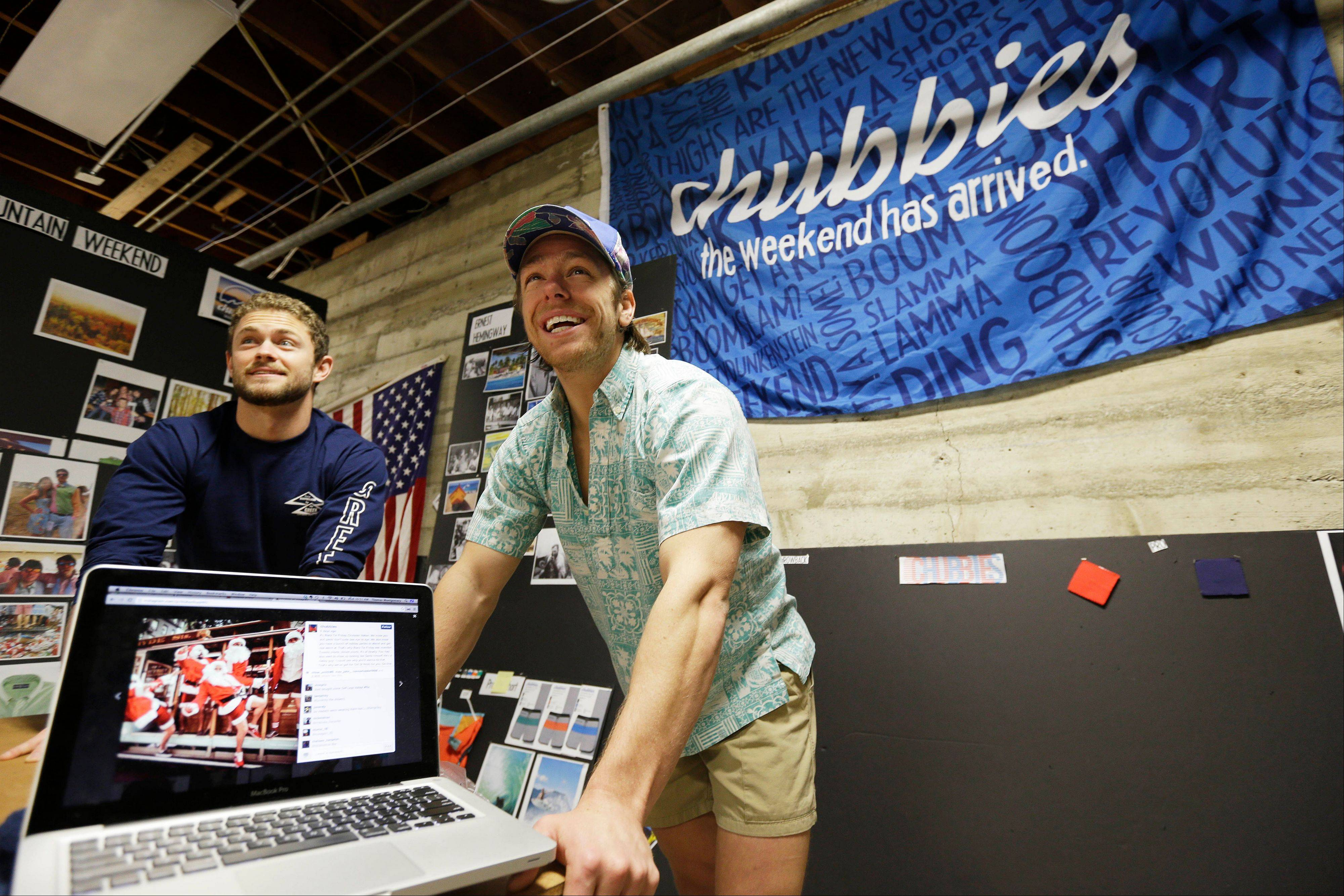Co-founders Tom Montgomery, left, and Preston Rutherford, right, stand behind a laptop showing an Instagram from a holiday photo shoot at the headquarters of Chubbies Shorts in San Francisco. Chubbies uses Facebook for marketing tools like videos that users will share with their friends. It uses Twitter for conversations with customers, and posts photos on Instagram to create buzz about their products.