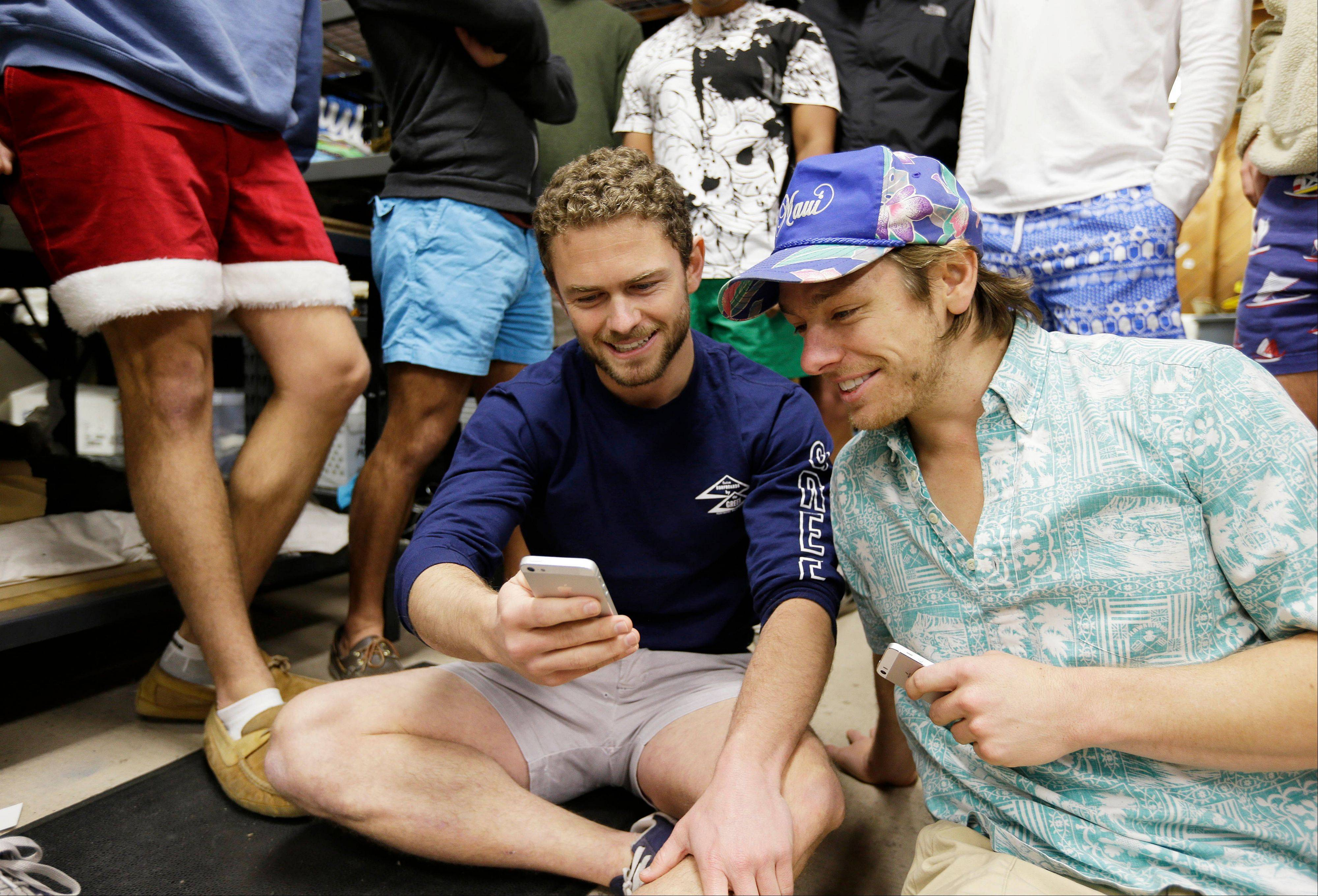 Co-founders Tom Montgomery, left, and Preston Rutherford, right, review Instagram performances while surrounded by co-workers at the headquarters of Chubbies Shorts in San Francisco. Chubbies uses Facebook for marketing tools like videos that users will share with their friends. It uses Twitter for conversations with customers, and posts photos on Instagram to create buzz about their products.