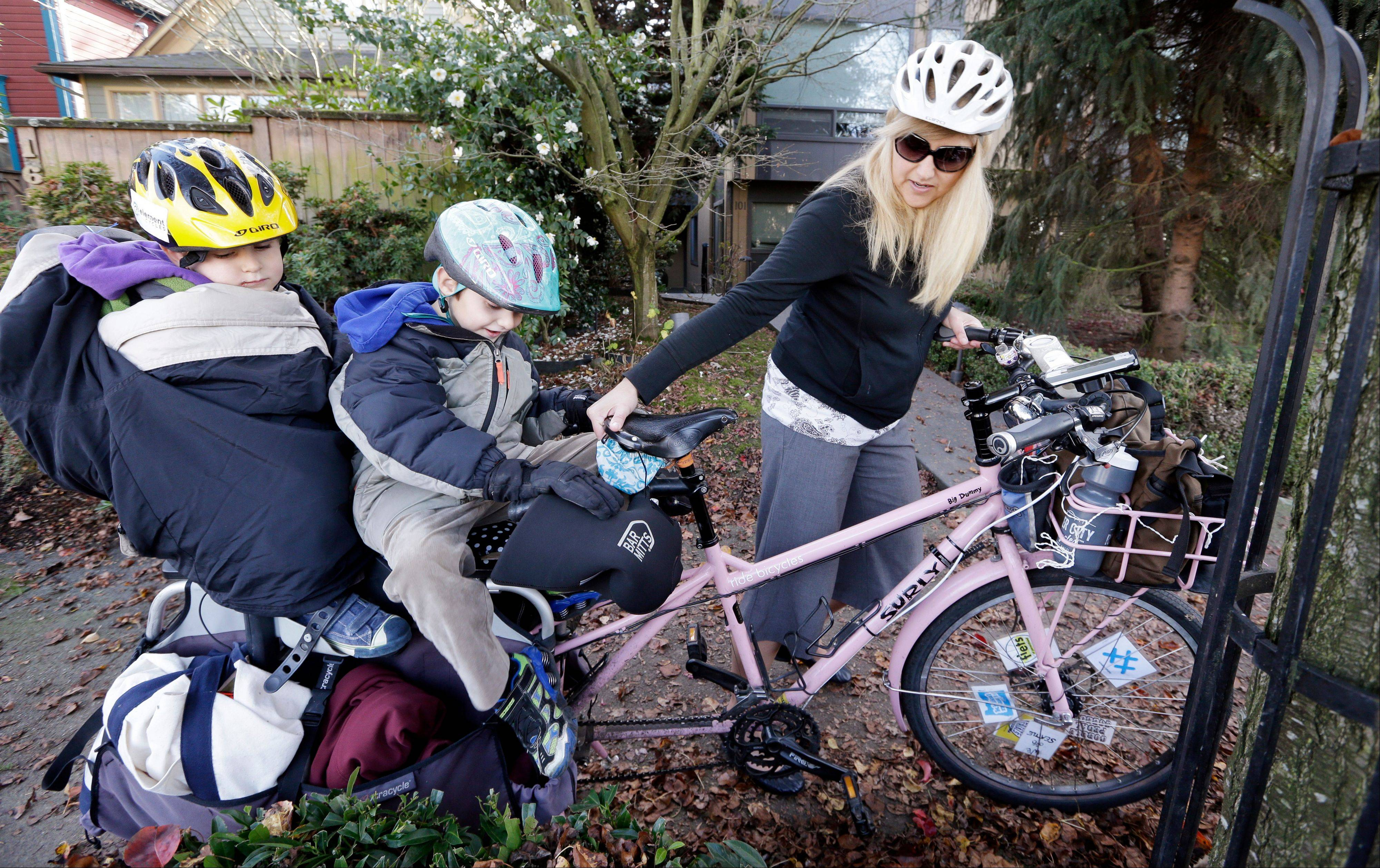 In this photo taken Nov. 27, 2013, Madi Carlson maneuvers the family cargo bike as her sons Rijder, 4, left, and Brandt, 6, sit aboard in Seattle. People in the Pacific Northwest are pushing the limits of what they can carry using so-called cargo bikes, shuttling children, groceries, fish and kegs of beer.