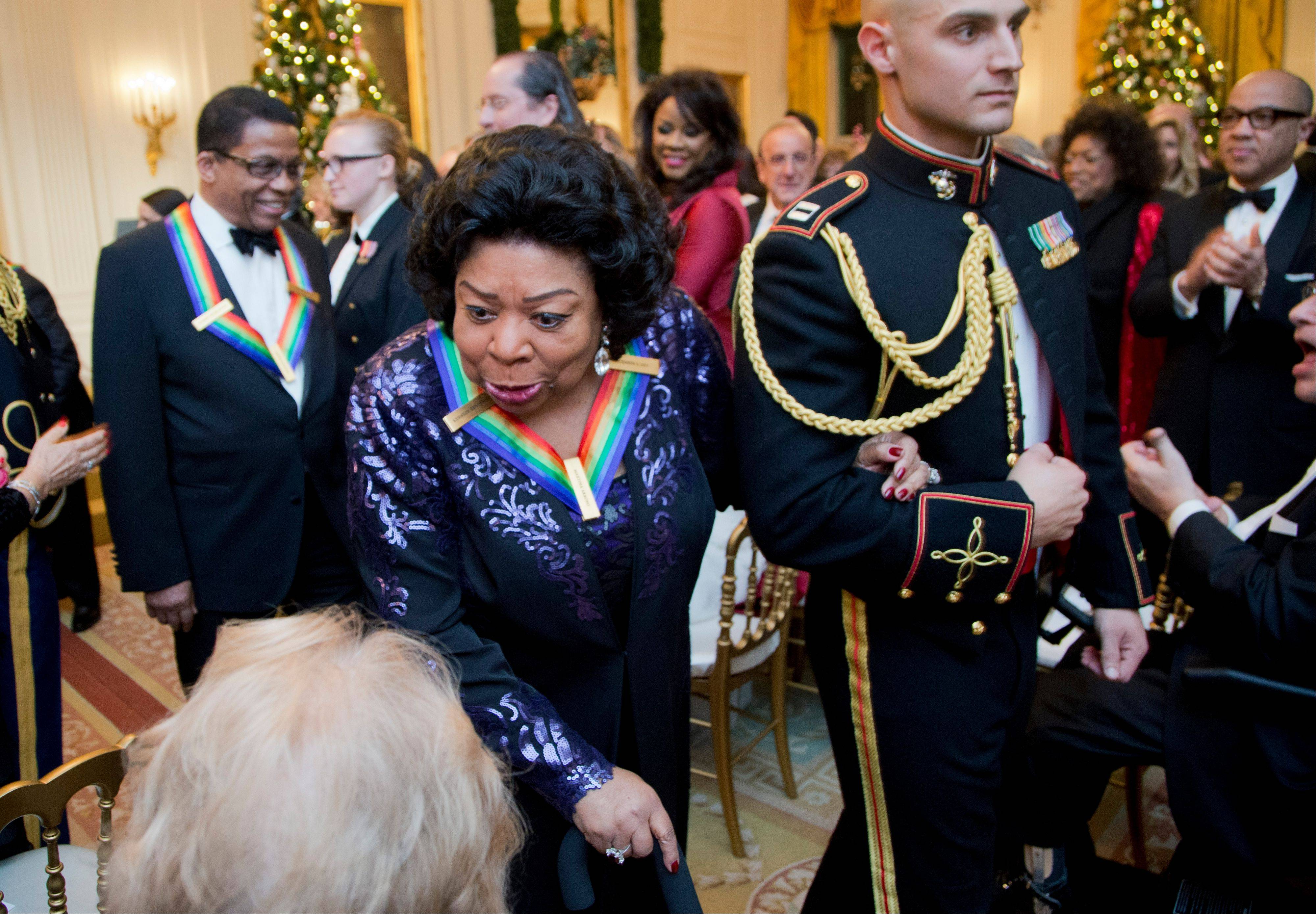 Recipient of the 2013 Kennedy Center Honors opera singer Martina Arroyo, left, leaves a reception Sunday honoring the 2013 Kennedy Center Honors honorees in the East Room of the White House in Washington.