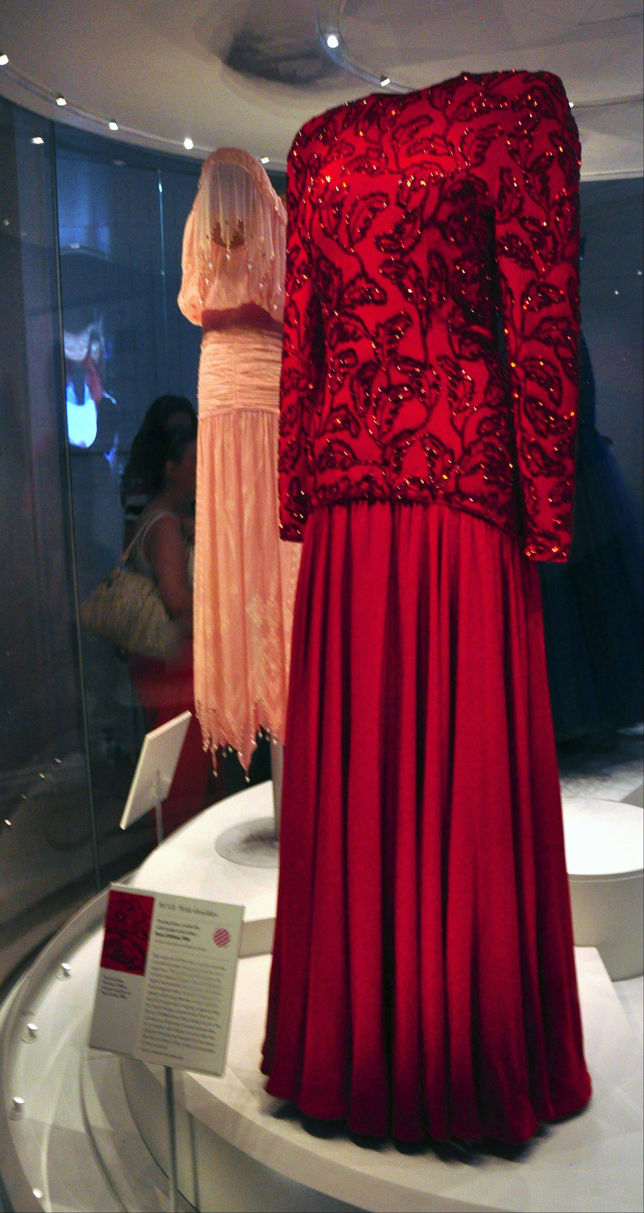 A red evening dress worn by Princess Diana during a royal tour of Saudi Arabia is one of 21 couture dresses in an exhibit at Kensington Palace.
