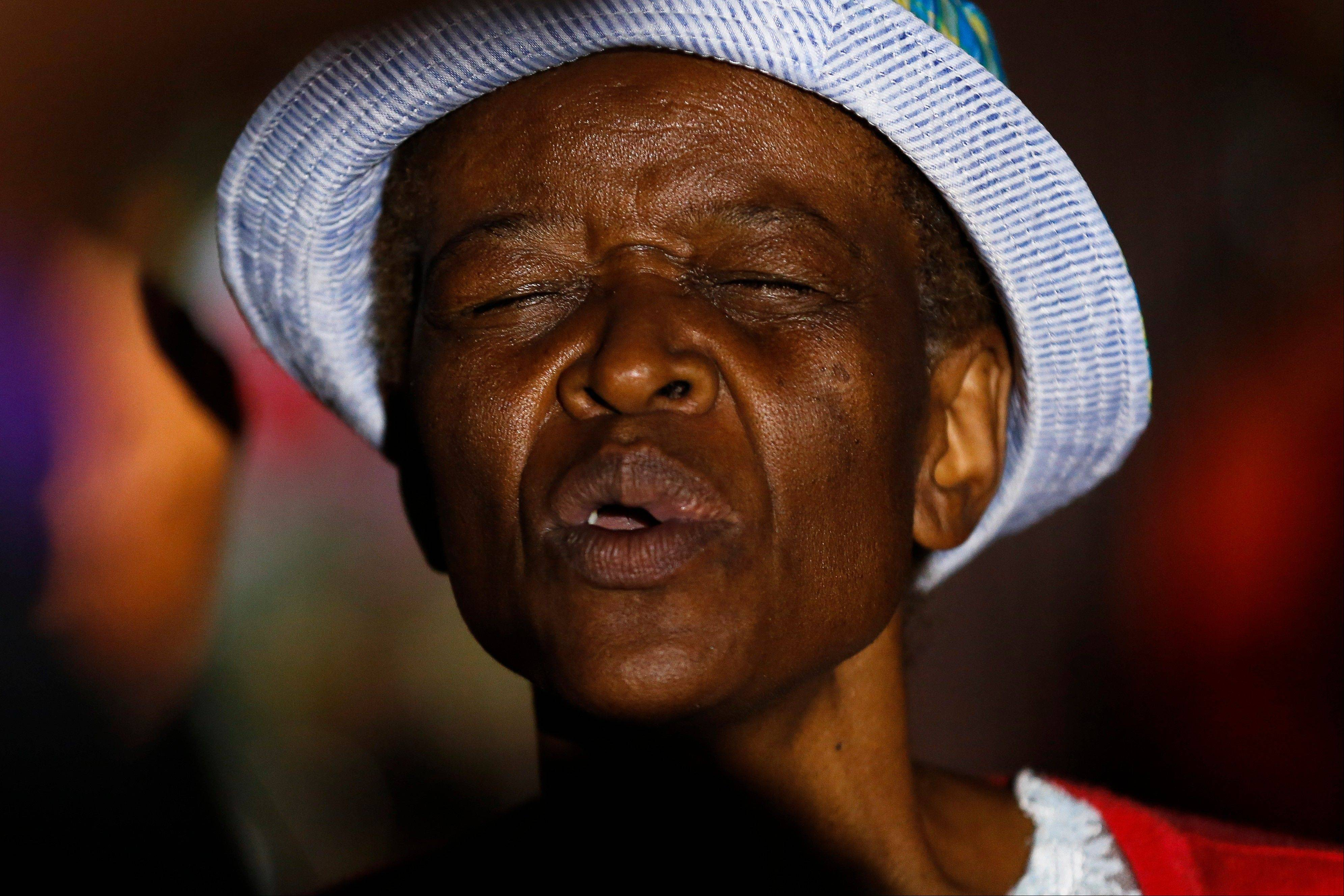 An elder woman prays for former South African President Nelson Mandela in the crowed street outside his old house in Soweto, Johannesburg, South Africa, Sunday.