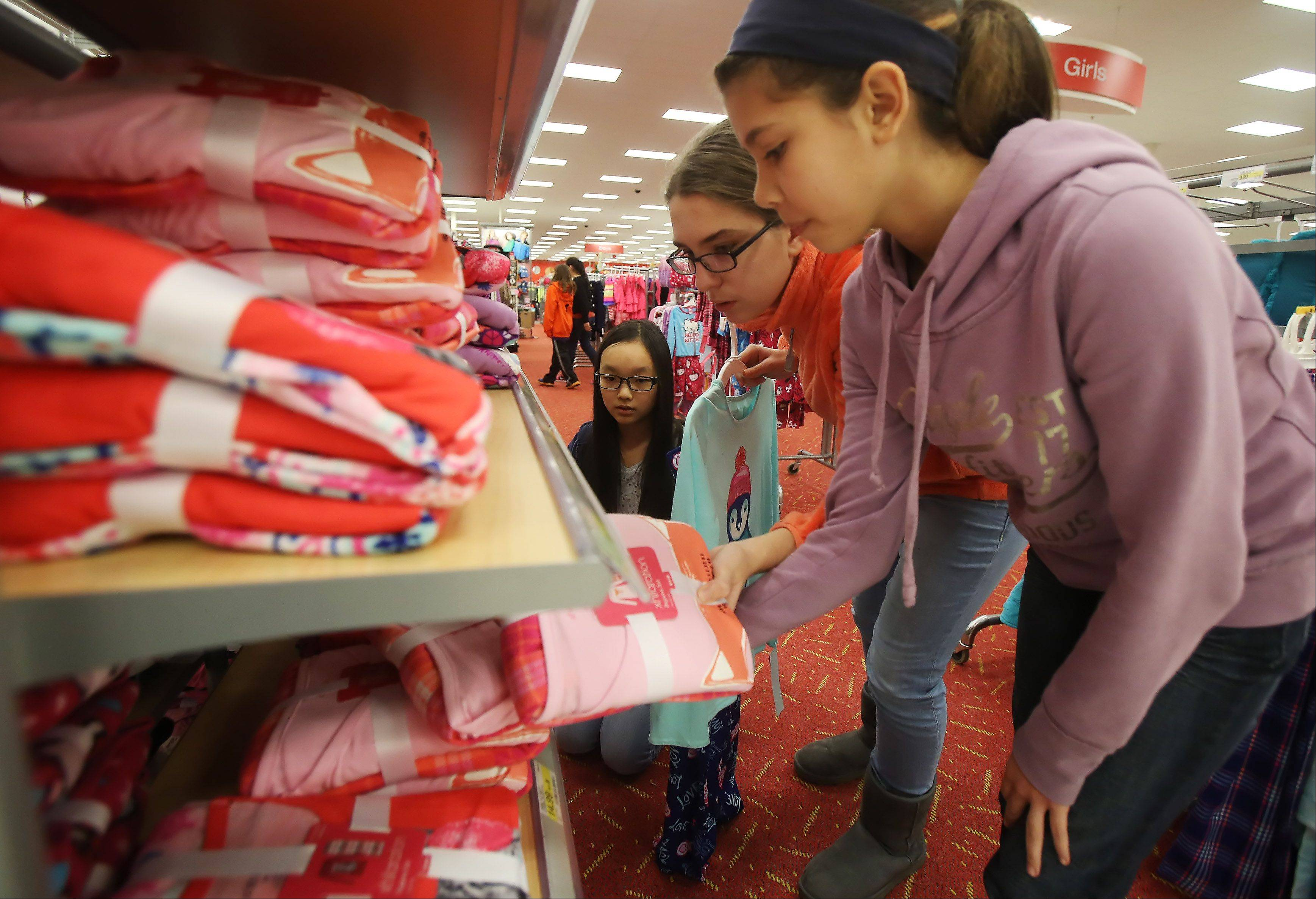 Seventh graders Stephanie Rivas, right, Julia Sulicka and Anna Lee, pick out pajamas as students from Carl Sandbug Middle School select toys and clothing from Target in Mundelein on Tuesday a needy Mundelein family. The Community Service Club raised $333 to help the family for the holidays.