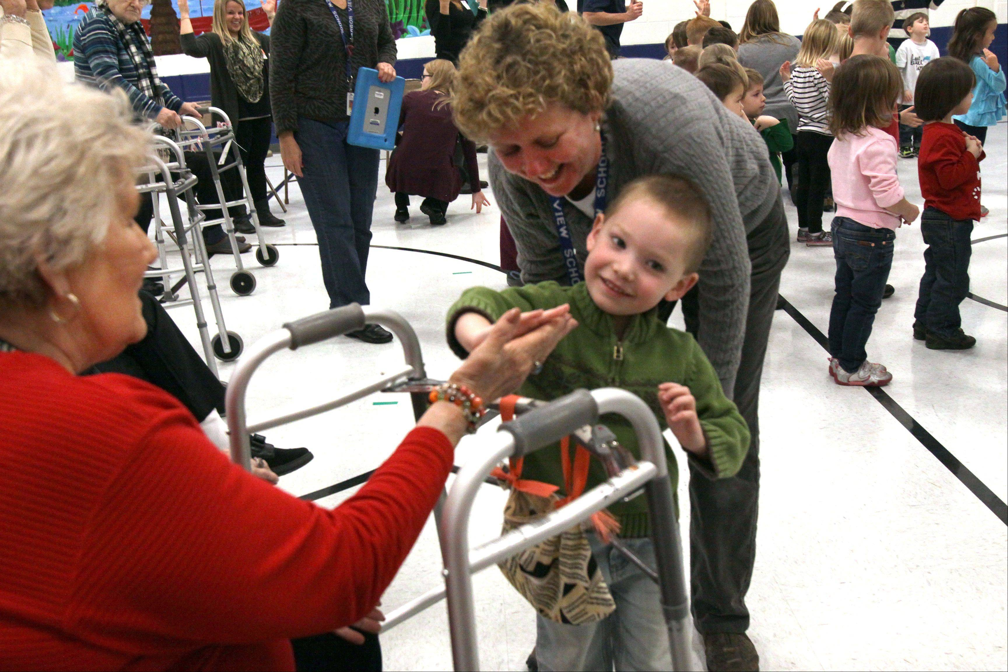 Carter Magnussan, 3, with a little help from his teacher Chris Gillis, gives Shirley Bouchez from Sunrise Senior Center, a high-five during their visit to Arbor View Elementary in Glen Ellyn on Wednesday.