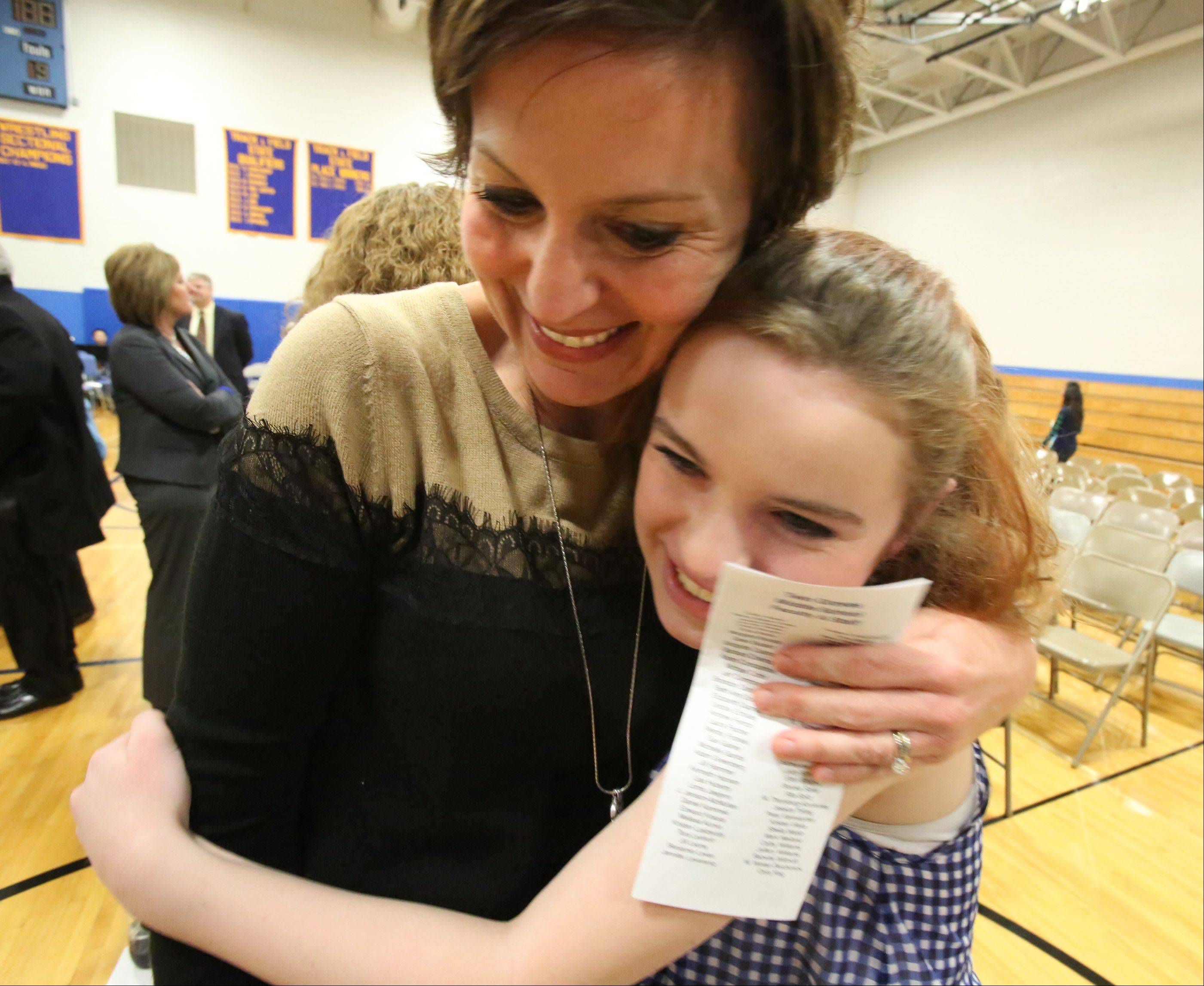 Former principal of Twin Groves Middle School, Heather Friziellie, receives a hug from sixth-grader Kira Sullivan after a program at the school celebrating the school winning a Blue Ribbon School award from the U.S. Dept. of Education on Thursday in Buffalo Grove.