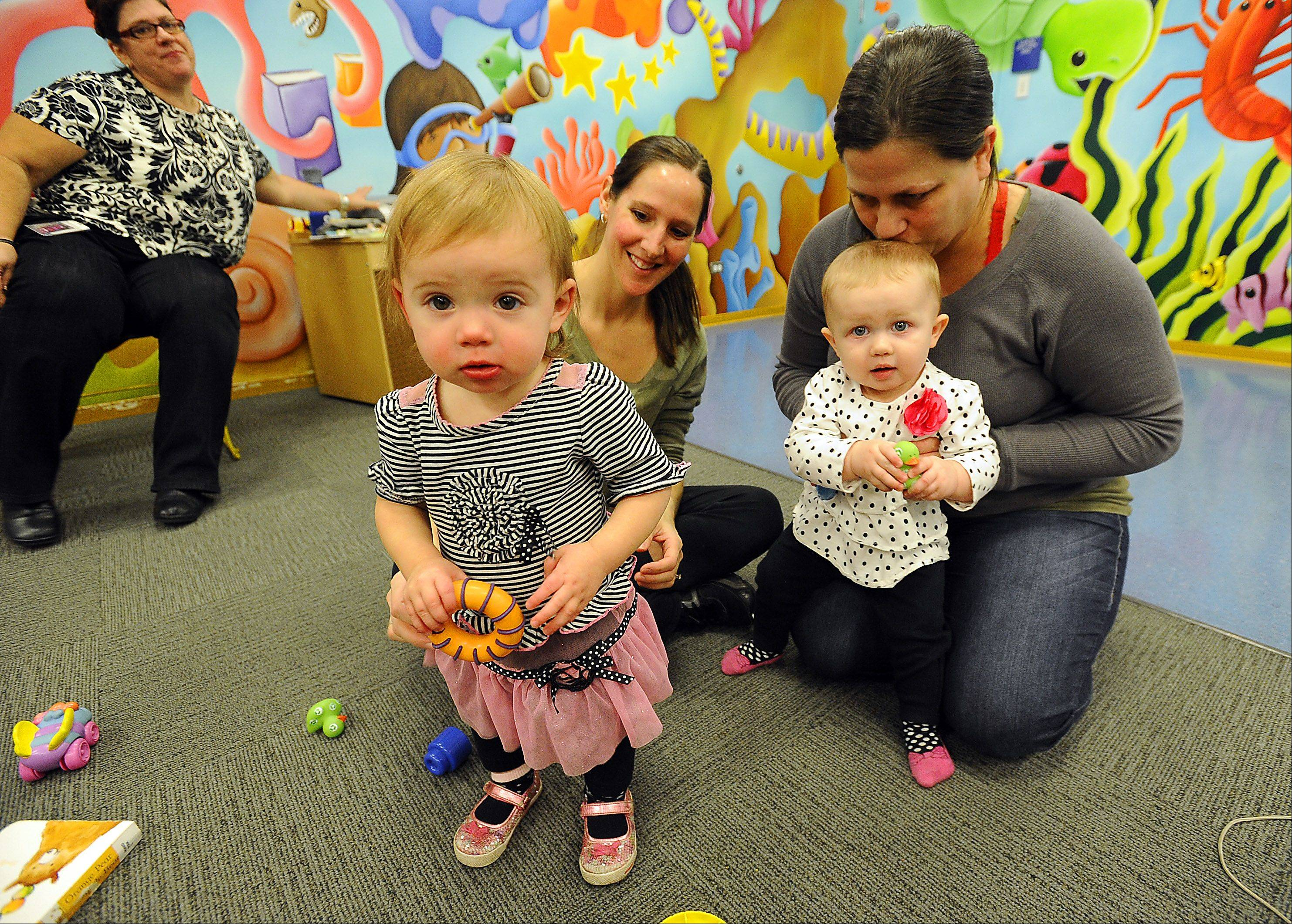 Irene Tripkos, left, Infant Toddler Specialist of District 62 Early Learning program, gets ready to start the class at the DesPlaines Public Library as Melissa Westphal and her 1 year old daughter Madeline, right, play with 1 year old Kensie Jewitt as her mother, Patty, looks on.