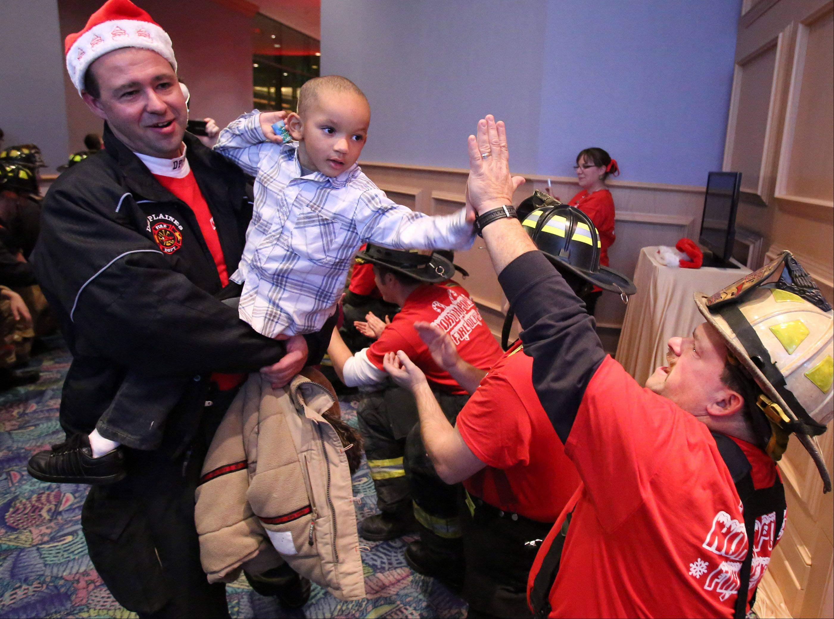 Mike Fox, district chief with the North Maine Fire Protection District, gives a high-five to Neko Rias, 4, of Chicago, being carried by Jim Utinans, engineer with Des Plaines Fire Department, through a Gauntlet of Honor made up of police officers and fire department personal into Santa's Winter Wonderland at the Donald E. Stephens Rosemont Convention and Banquet Center on Saturday in Rosemont.