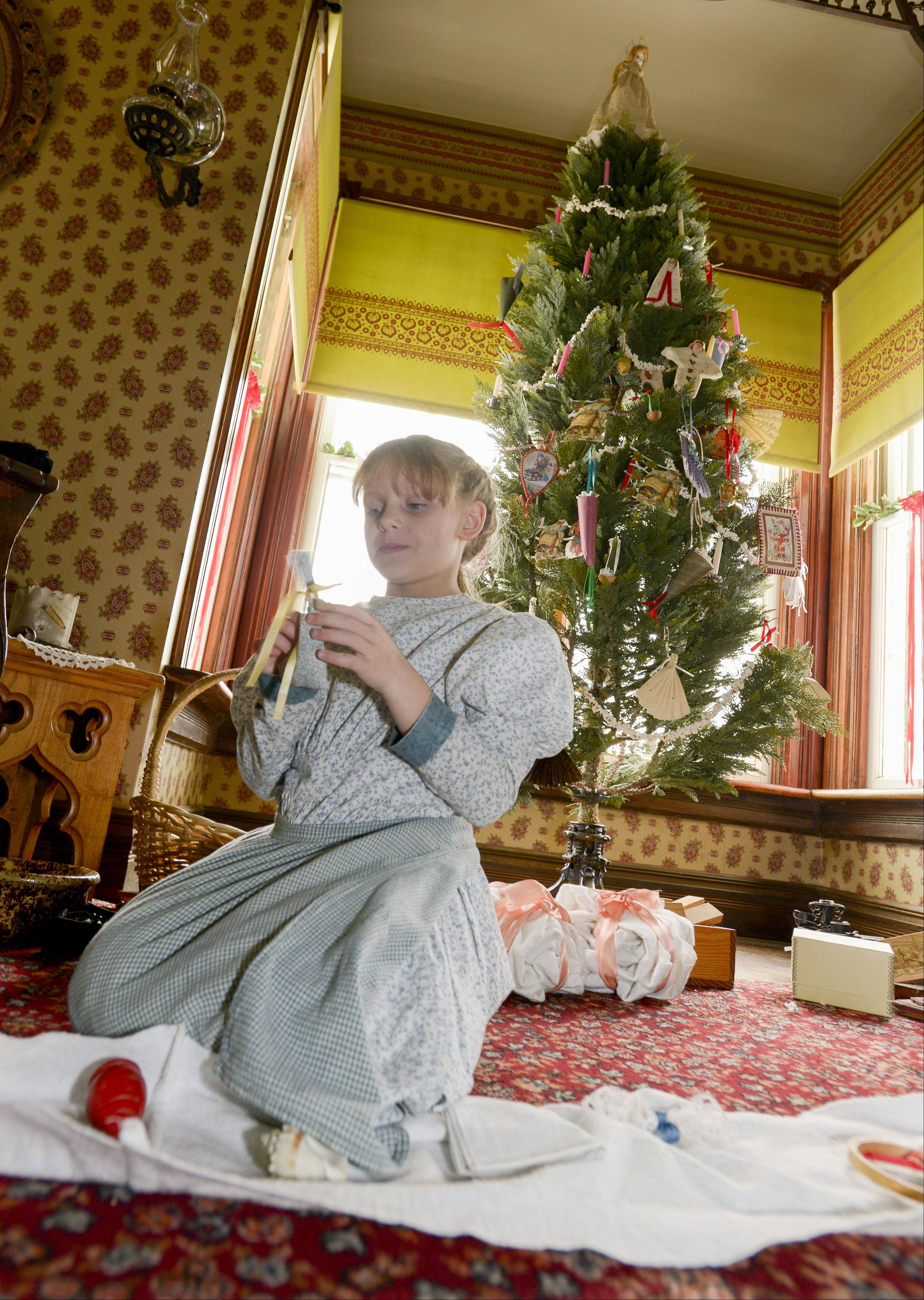 Annemarie Zimmerman, 7, of Wheaton plays near a traditional 1890s Christmas tree on display Sunday at Kline Creek Farm. The farm is offering visitors a tour showing how people living in what are now Chicago's suburbs would have celebrated the holidays more than 120 years ago.