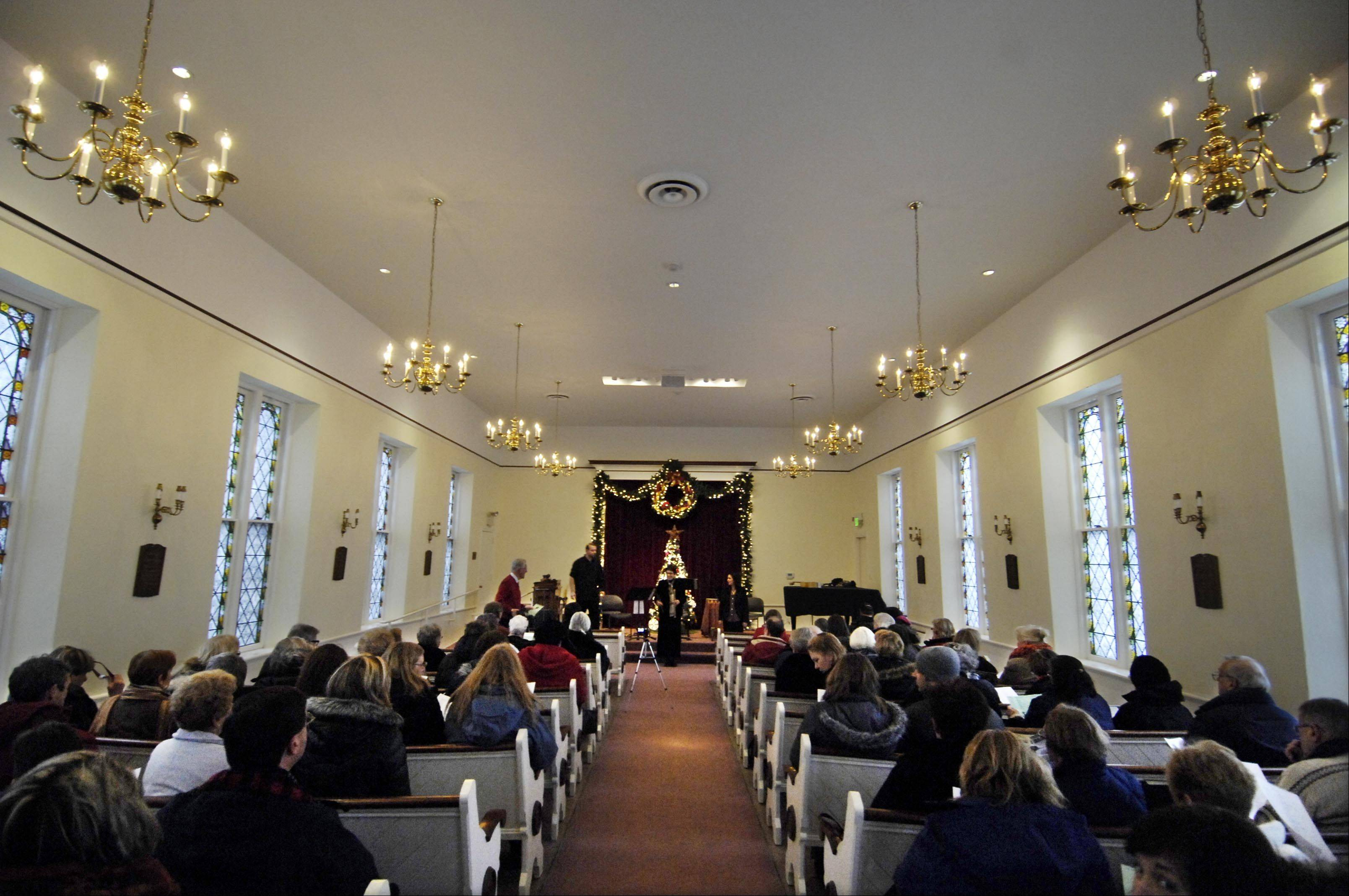 The pews in the oldest church in Geneva, the Unitarian Universalist Society of Geneva, were salvaged from a church that burned in the 1871 Chicago fire. The building was originally built in 1843. Visitors listened to a performance of Renaissance and Baroque music by EnsAmble Ad-Hoc on Sunday during the city's Steeple Walk.