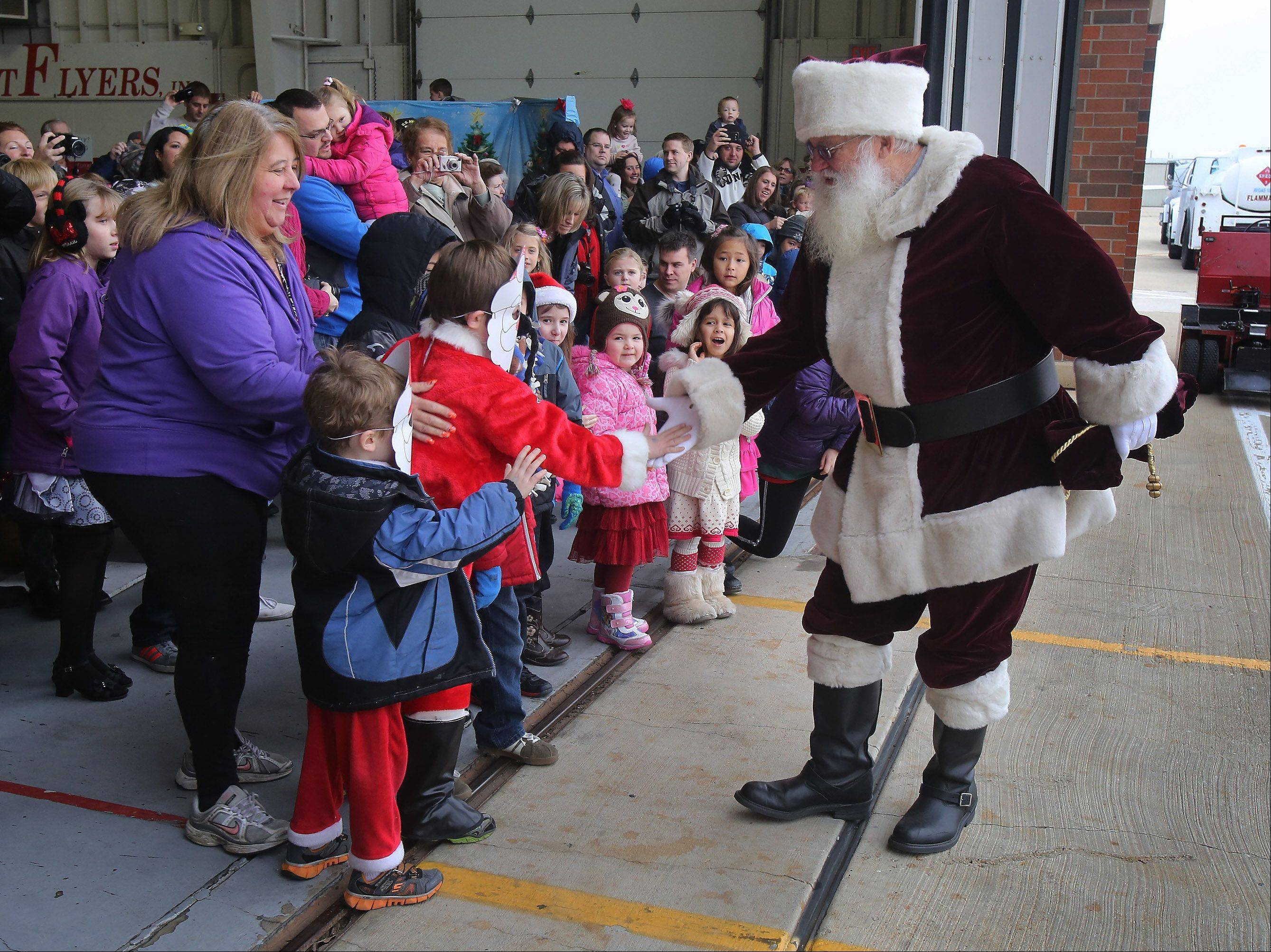 "Santa Claus greets children at the Schaumburg Regional Airport after arriving by helicopter Sunday for ""Santa's Flight to Schaumburg."" The holiday event was sponsored by the Schaumburg Park District and Northwest Flyers. About 300 visitors attended the event, which included a breakfast buffet, games and crafts."