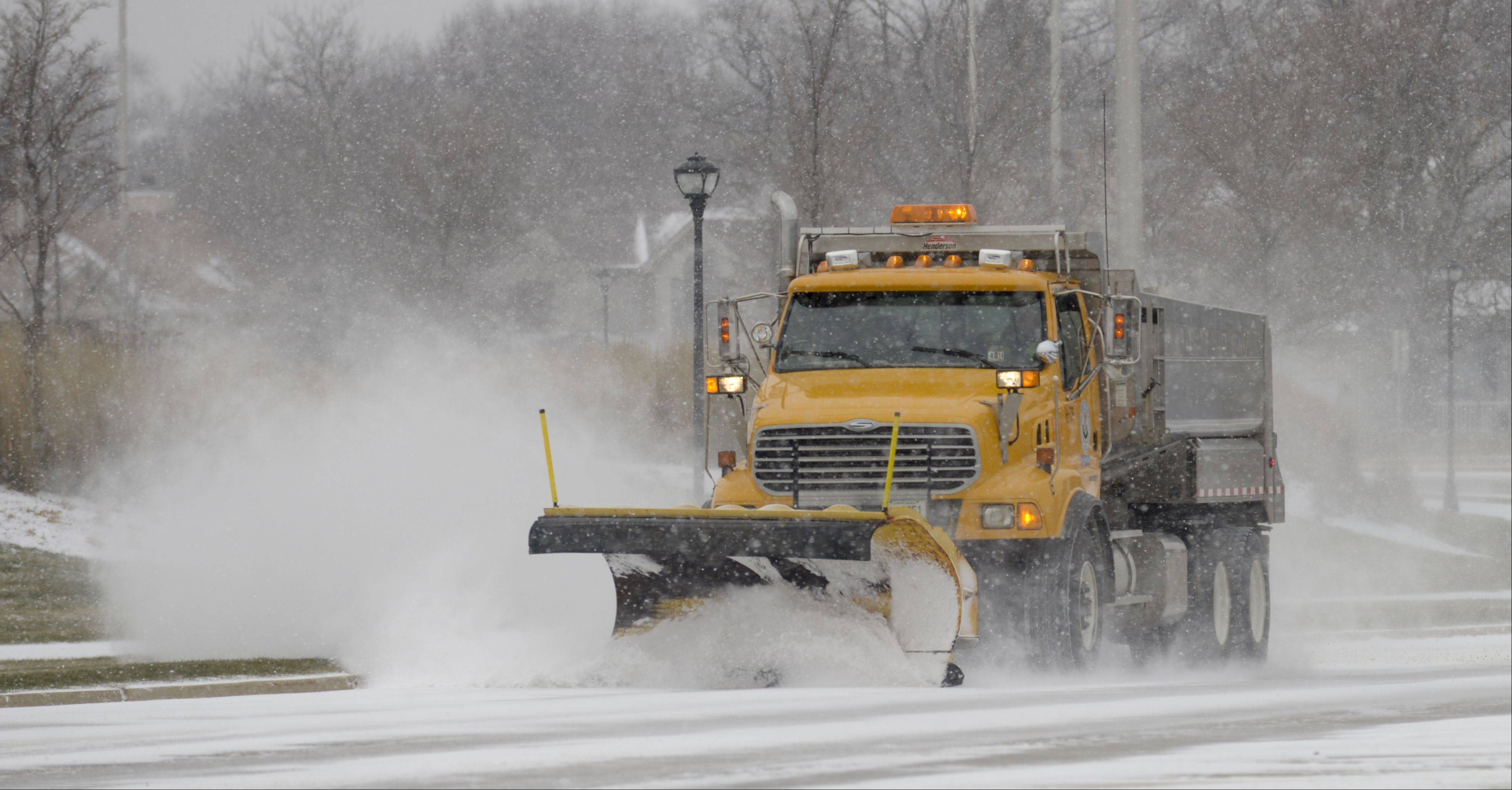 A DuPage County snowplow cleans the roads in Warrenville as Sunday's snowfall brought sometimes treacherous driving conditions to the area.