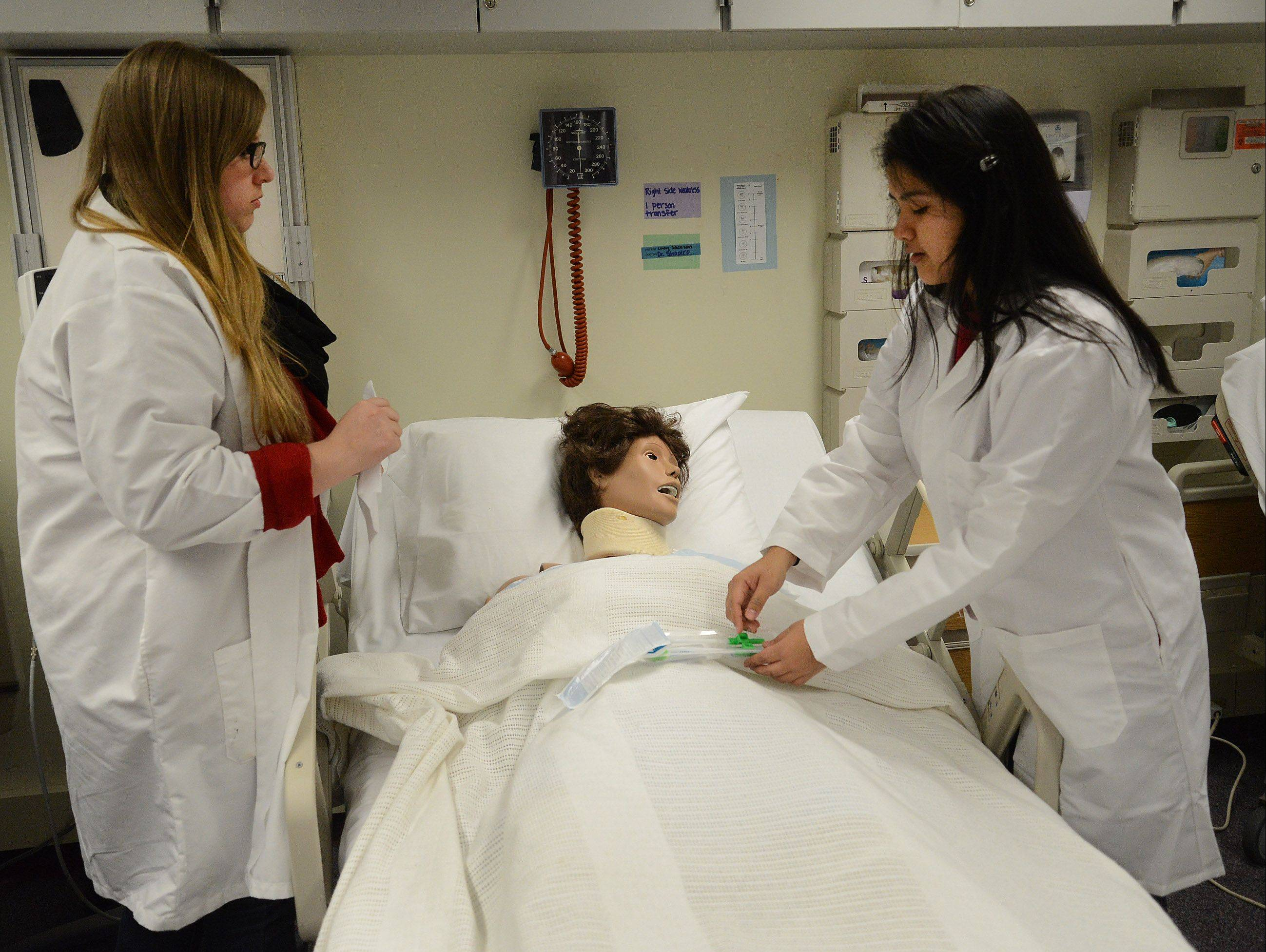 Aneta Polak, left, and Stefany Lima practice patient care in the nursing lab classroom at Wheeling High School.