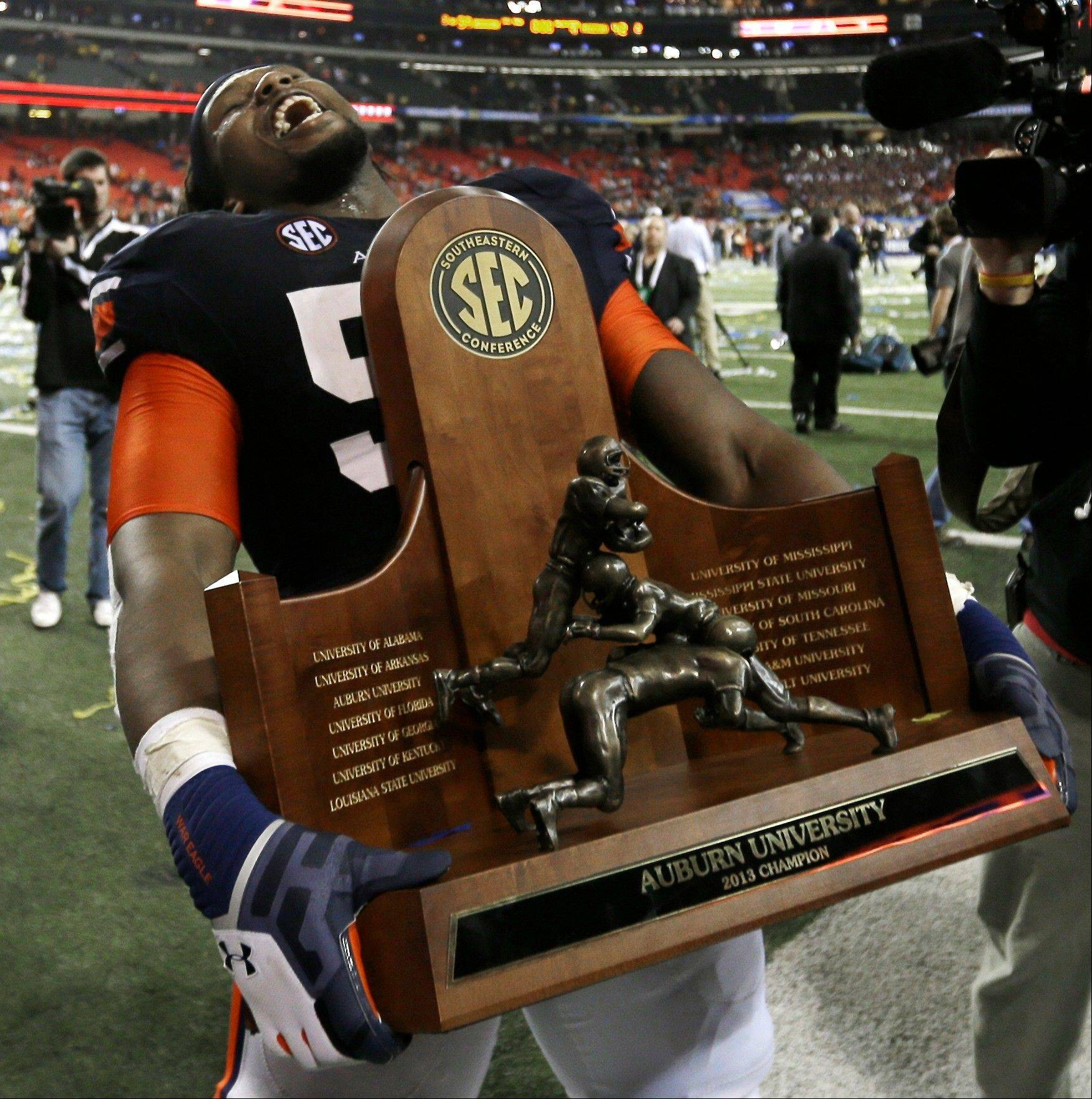 Auburn offensive linesman Avery Young (56) carries the championship trophy after the second half of the Southeastern Conference NCAA football championship game against Missouri, Saturday, Dec. 7, 2013, in Atlanta. Auburn won 59-42.