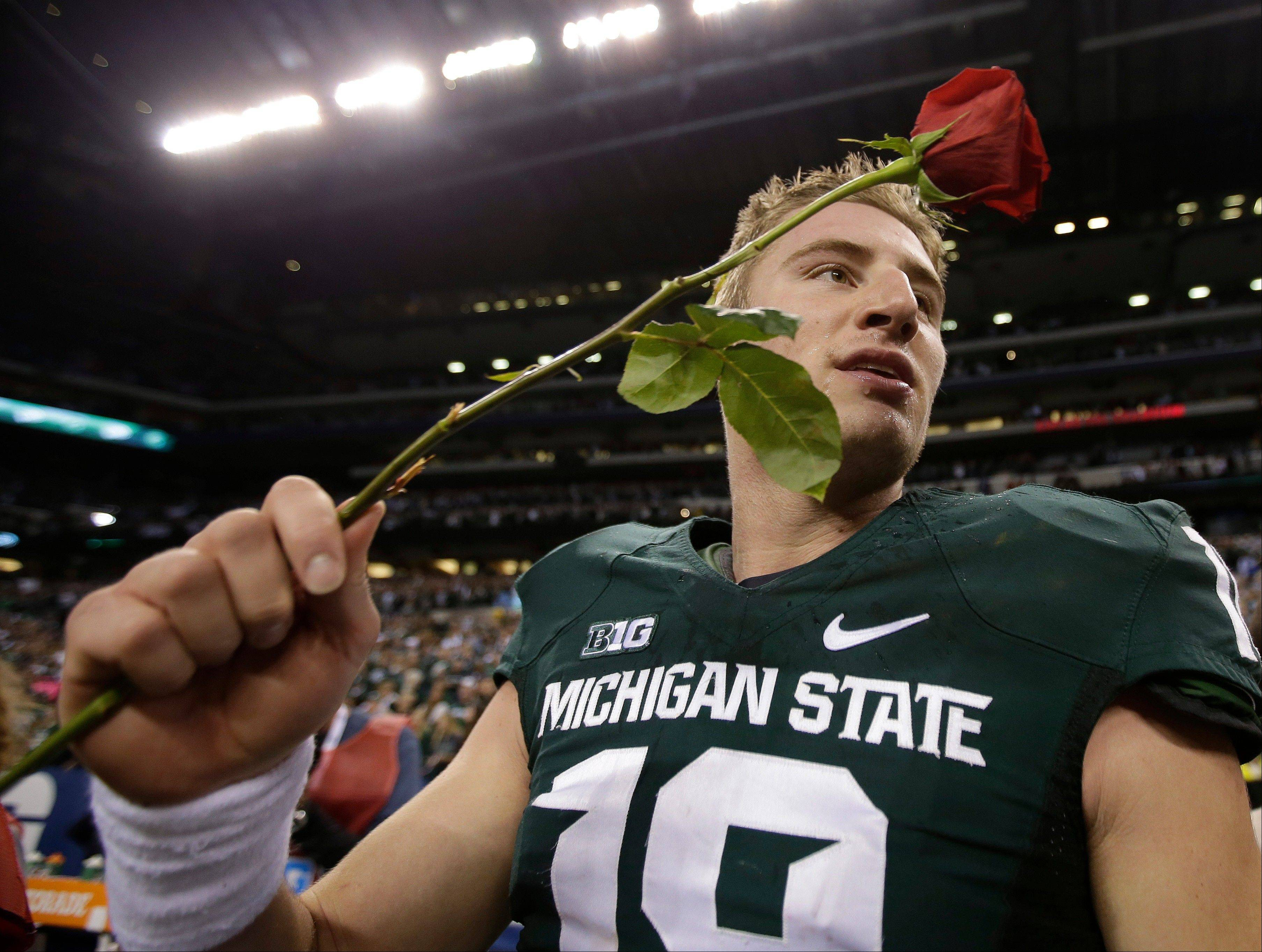 Michigan State's Connor Cook holds a rose after Michigan State defeated Ohio State, 34-24 in the Big Ten Conference championship NCAA college football game Saturday Dec. 7, 2013, in Indianapolis.