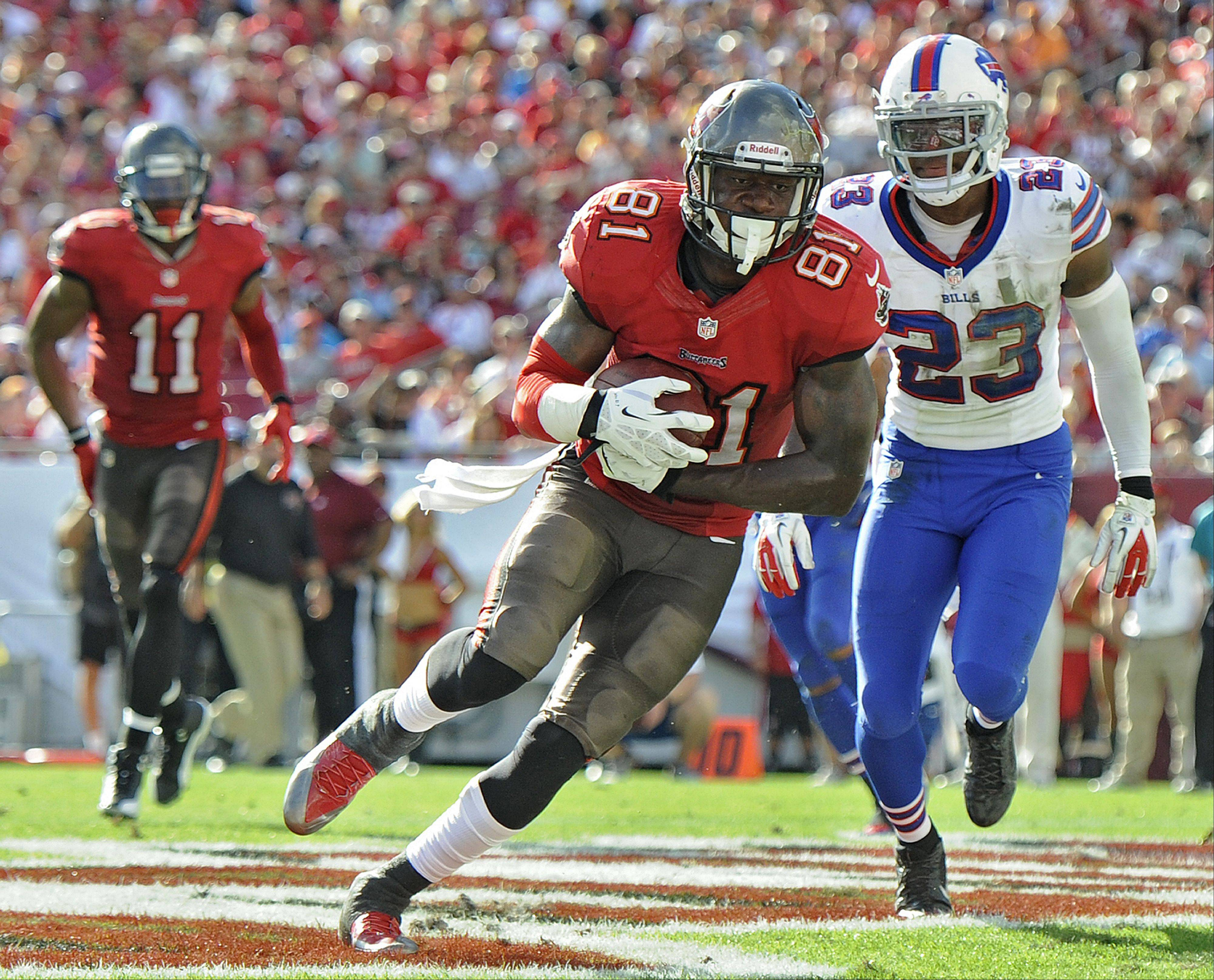Tampa Bay Buccaneers tight end Timothy Wright (81) scores past Buffalo Bills free safety Aaron Williams (23) on a five-yard touchdown reception during the second quarter of an NFL football game Sunday, Dec. 8, 2013, in Tampa, Fla.