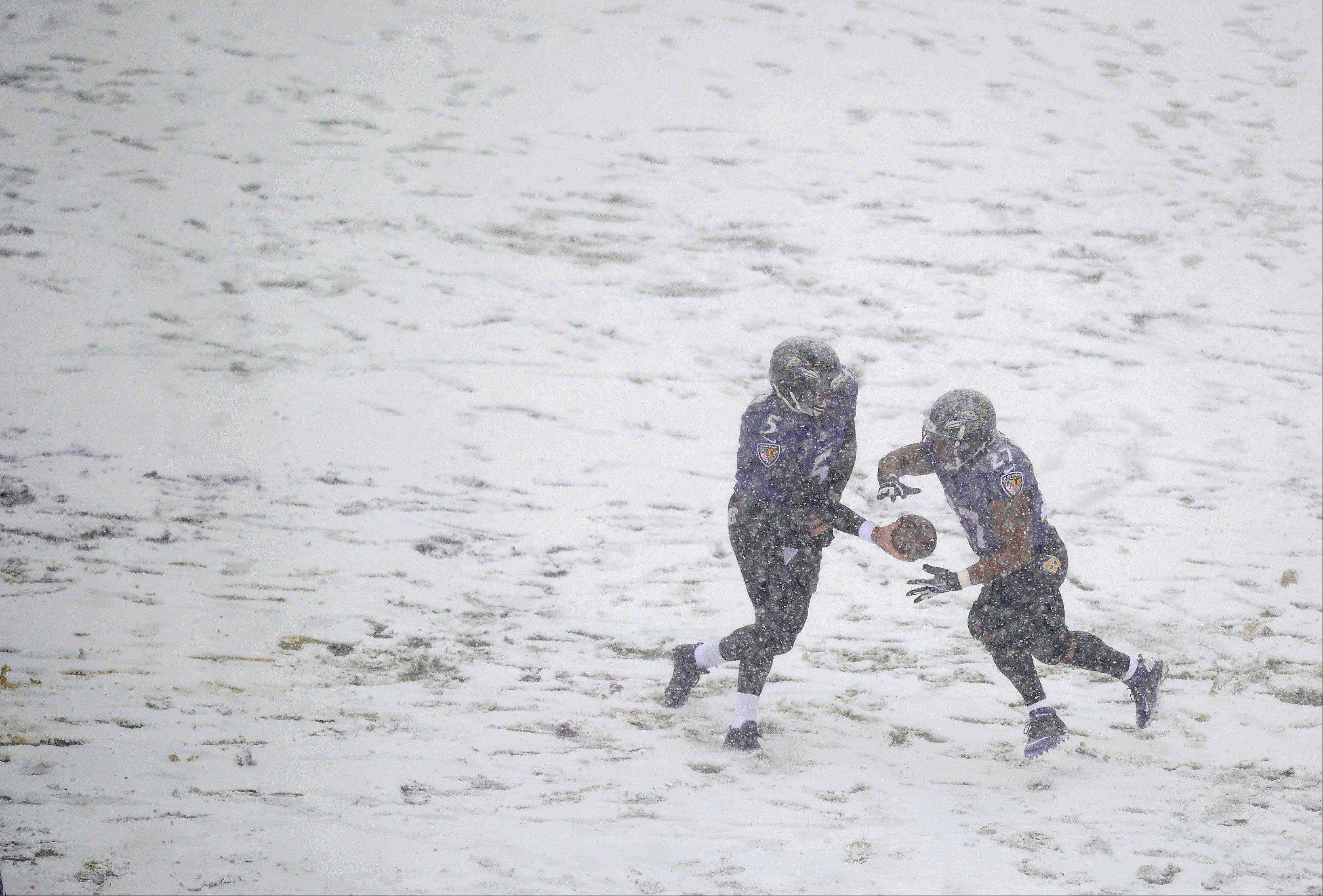 Baltimore Ravens quarterback Joe Flacco, left, hands the ball off to running back Ray Rice as snow falls in the first half of an NFL football game against the Minnesota Vikings, Sunday, Dec. 8, 2013, in Baltimore.