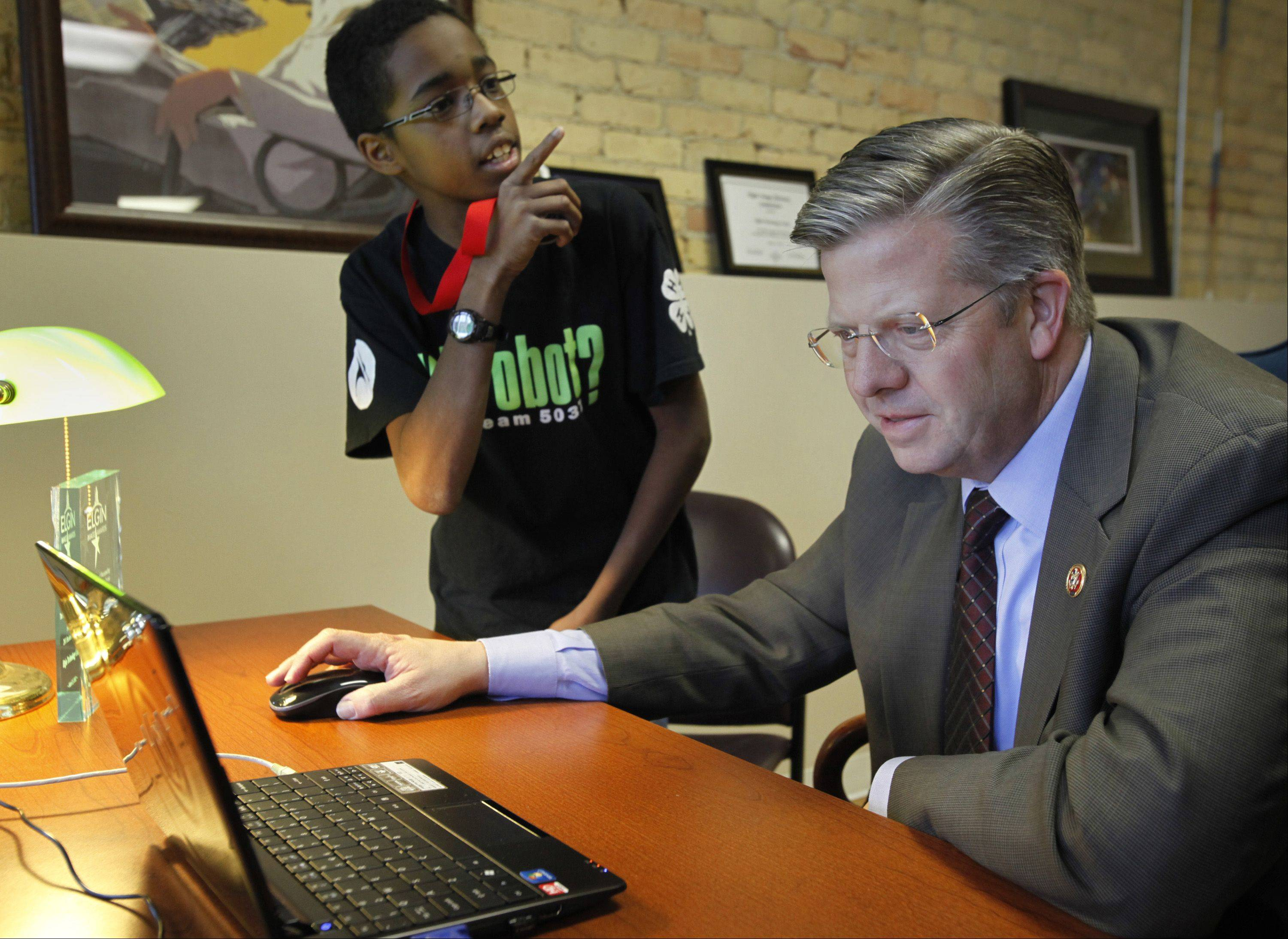 U.S. Rep. Randy Hultgren works with 12-year-old Patrick Stephen of Elgin to create lines of code at Elgin Technology Center for a simulated computer game.