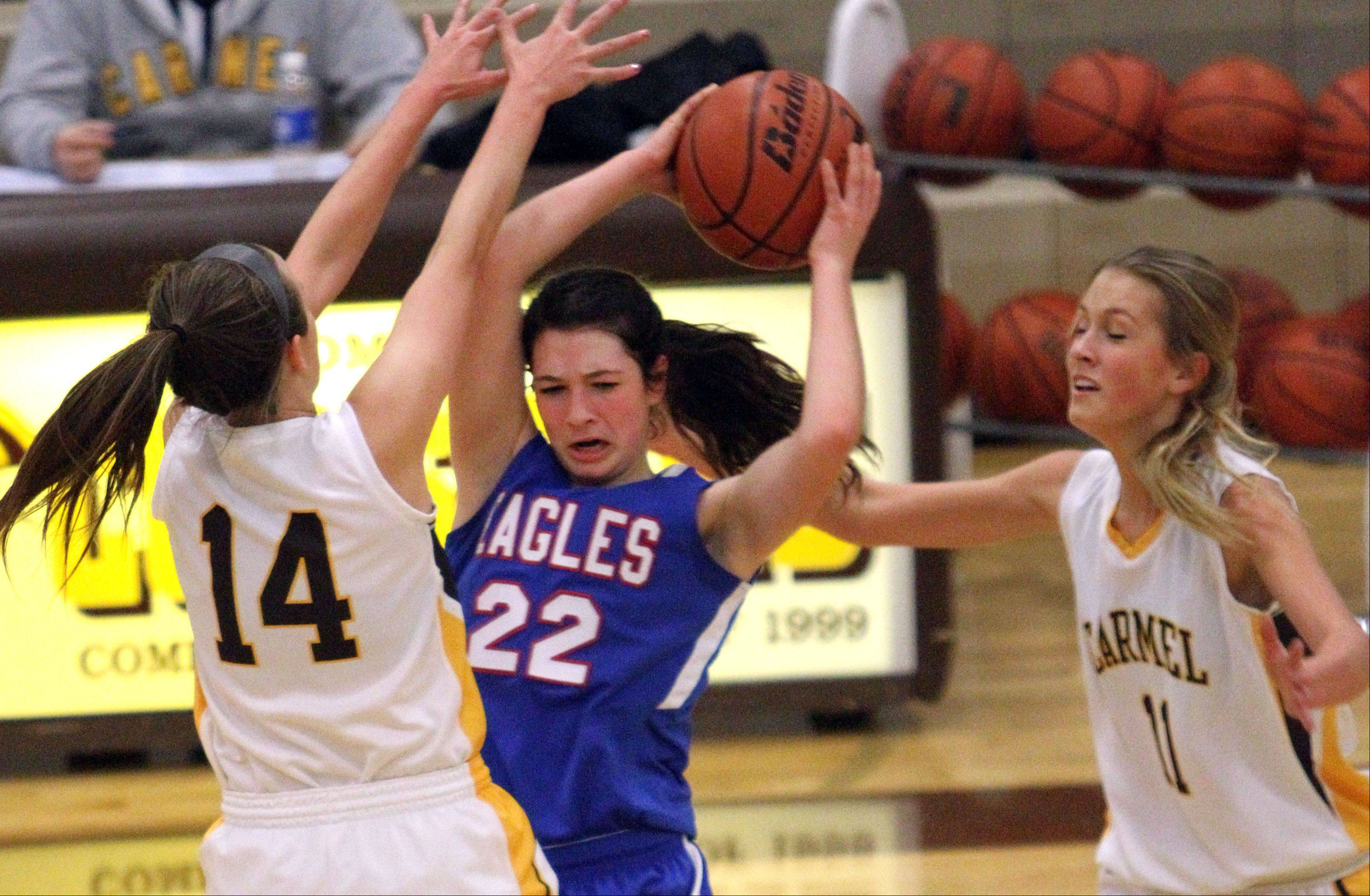 Lakes' Ellie Haviland, middle, gets trapped by Carmel's Cassidy Kloss, left, and Leah Lach on Monday night at Carmel Catholic.