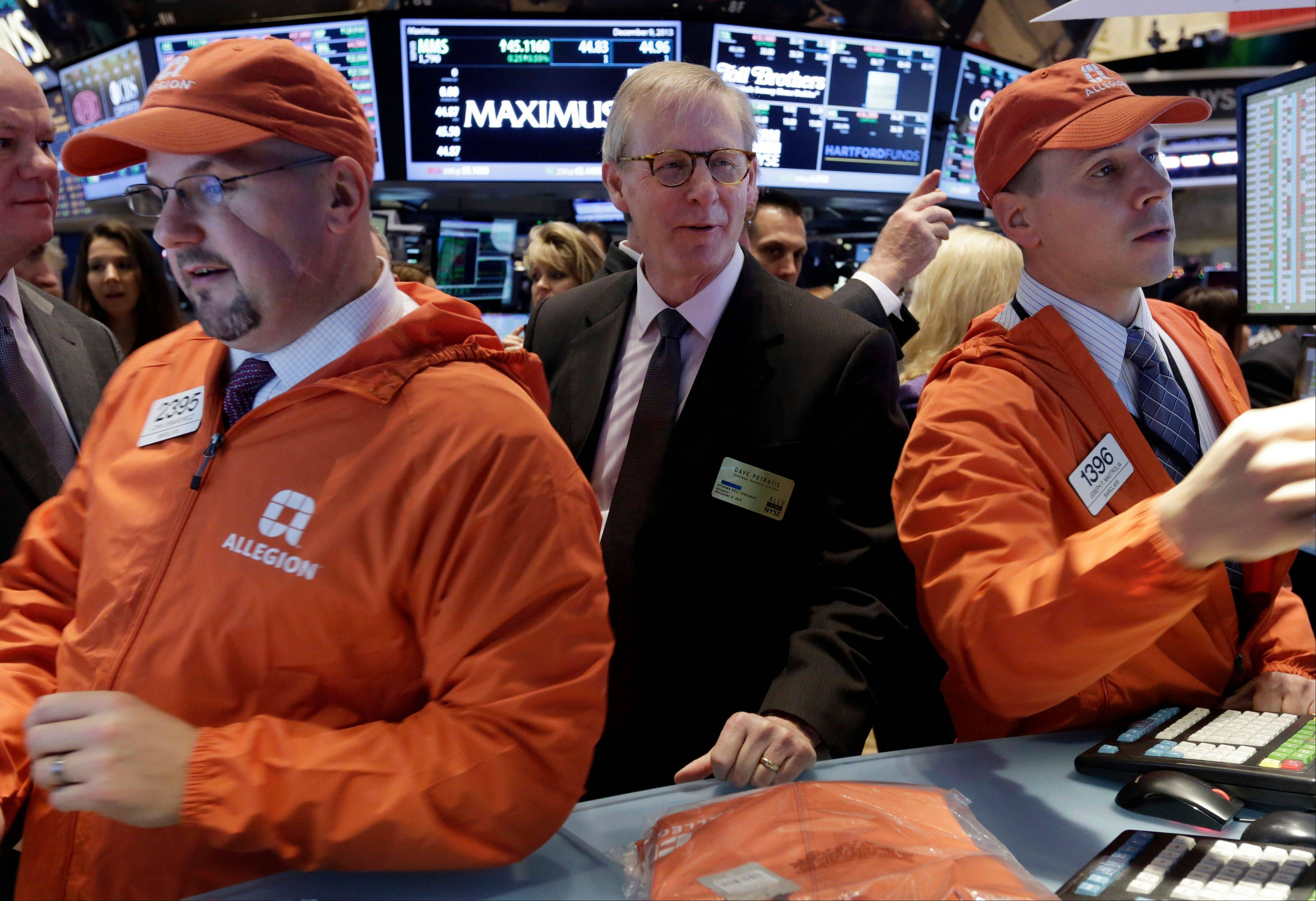 Allegion Chairman, president and CEO Dave Petratis, center, visits a post on the floor of the New York Stock Exchange as his company's stock makes its debut as a stand-alone, publicly-traded company following its spinoff from Ingersoll Rand on Monday