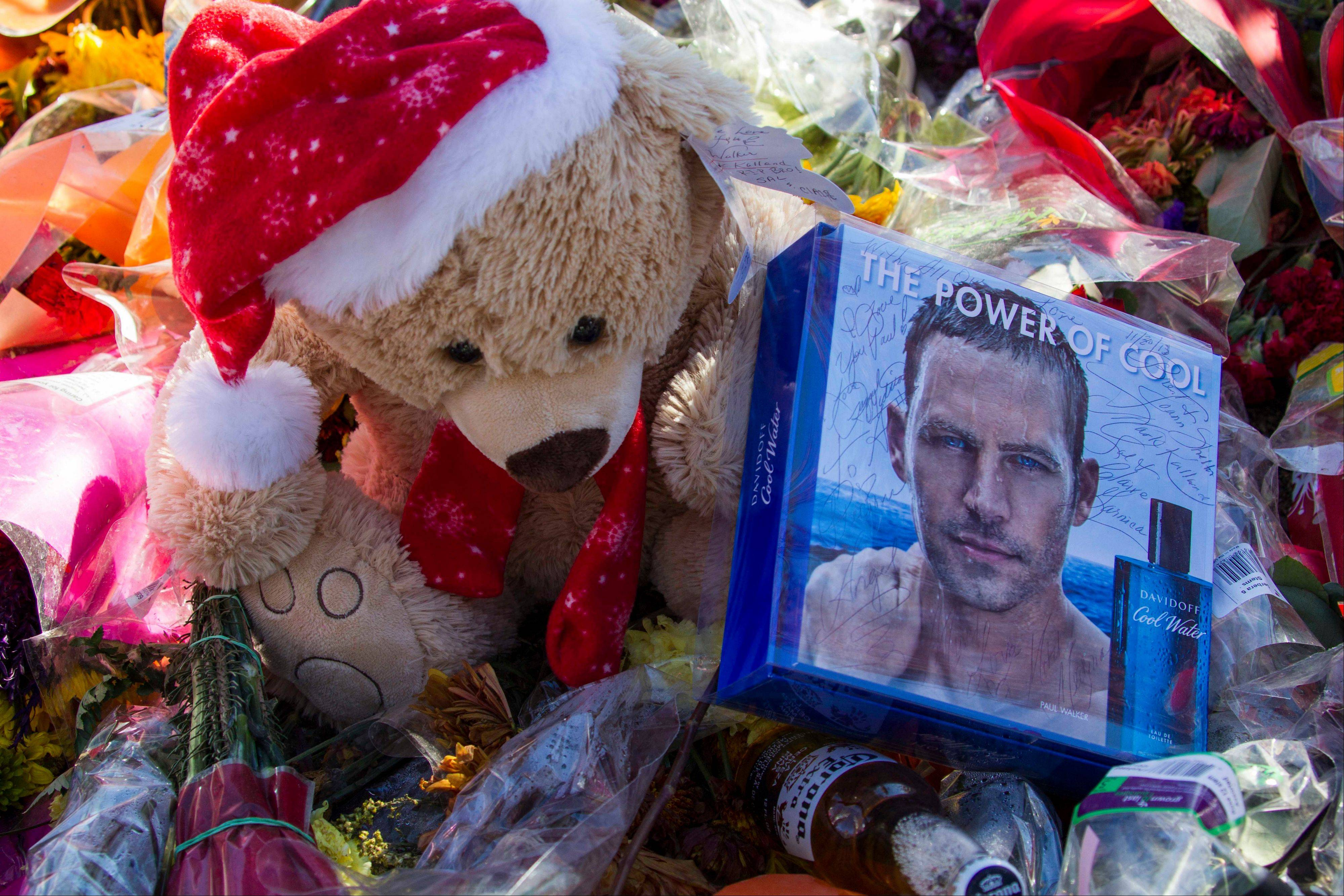 Flowers and messages are left at a memorial rally and car cruise in Valencia, Calif., Sunday to remember actor Paul Walker and his friend Roger Rodas, who died in a fiery car crash last Saturday.