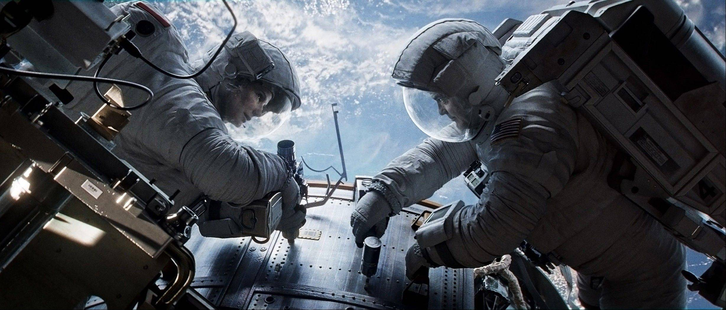"This publicity photo released by Warner Bros. Pictures shows Sandra Bullock, left, as Dr. Ryan Stone and George Clooney as Matt Kowalsky in ""Gravity."" The space odyssey ""Gravity"" and the futuristic romance ""Her"" have tied for best picture from the Los Angeles Film Critics Association. The LA critics announced their picks Sunday with voting culminating in a tie for the group's top honor. ""Gravity"" led with a total of four awards, including picks for best directing, best editing and best cinematography."