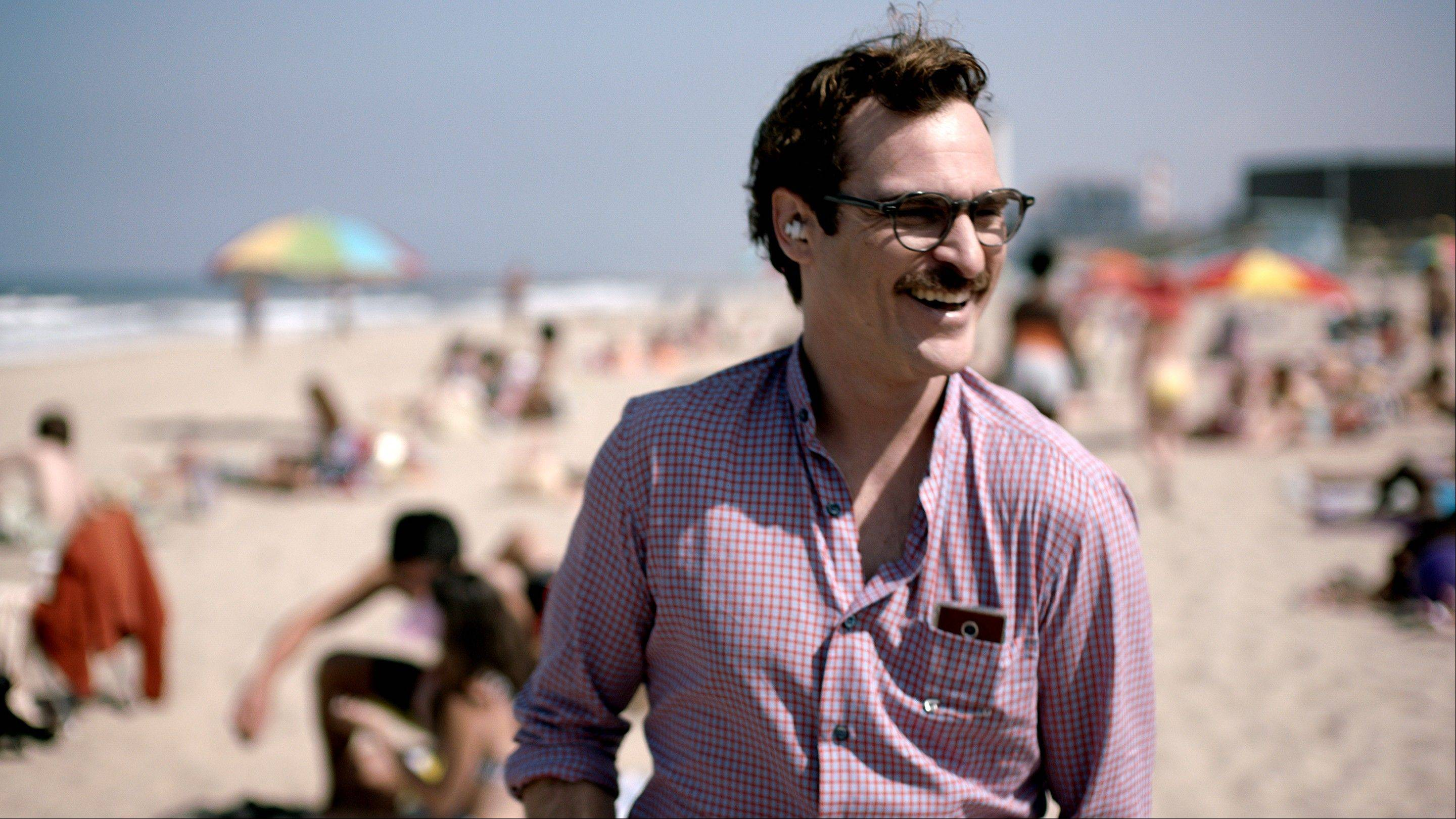 "This undated file image released by Warner Bros. Pictures shows Joaquin Phoenix in a scene from ""Her."" The space odyssey ""Gravity"" and the futuristic romance ""Her"" have tied for best picture from the Los Angeles Film Critics Association. The LA critics announced their picks Sunday, with voting culminating in a tie for the group�s top honor. Spike Jonze's ""Her"" also won best production design for K.K. Barrett�s sleek, near-future designs."