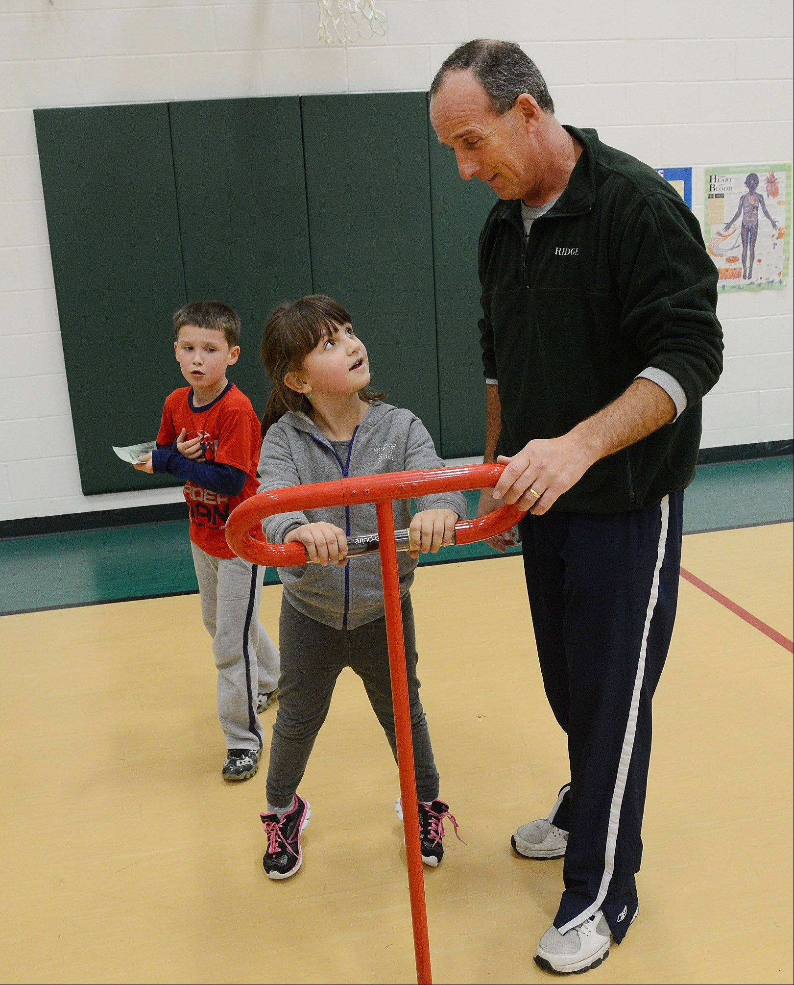 Ridge Family Center for Learning P.E. teacher Will Hogan helps student Maria Irimia check her heart rate on a digital monitor. The goal during a recent cardio day in gym class was to maintain a heart rate above 125 beats per minute.