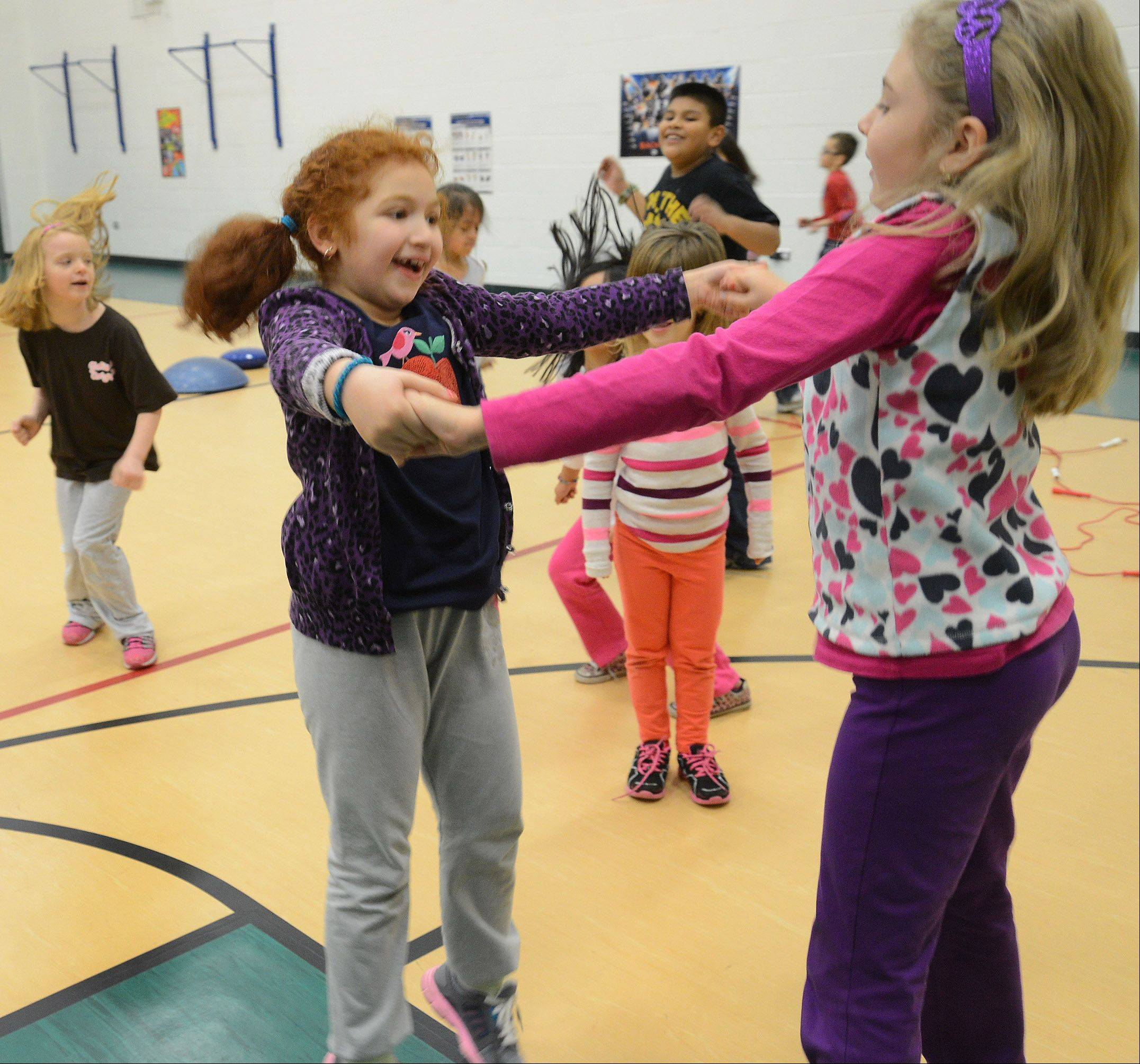 Leann Shaya, left, and Natalie Rybinski exercise during one of Will Hogan's recent P.E. classes at the Ridge Family Center for Learning in Elk Grove Village.